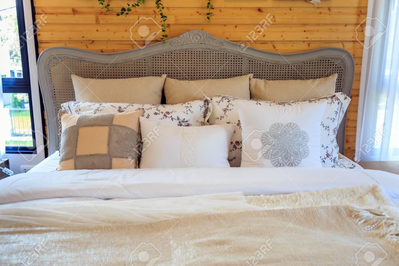 Schöne Kissen Und Beige Decke Auf Einem Bett Mit Holzwand Und Weißen  Jalousien Im Schlafzimmer Standard