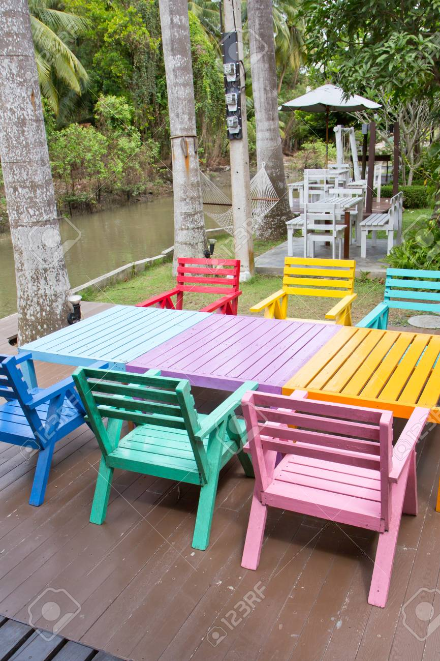 Colorful wooden armchairs beside a river stock photo 45366670