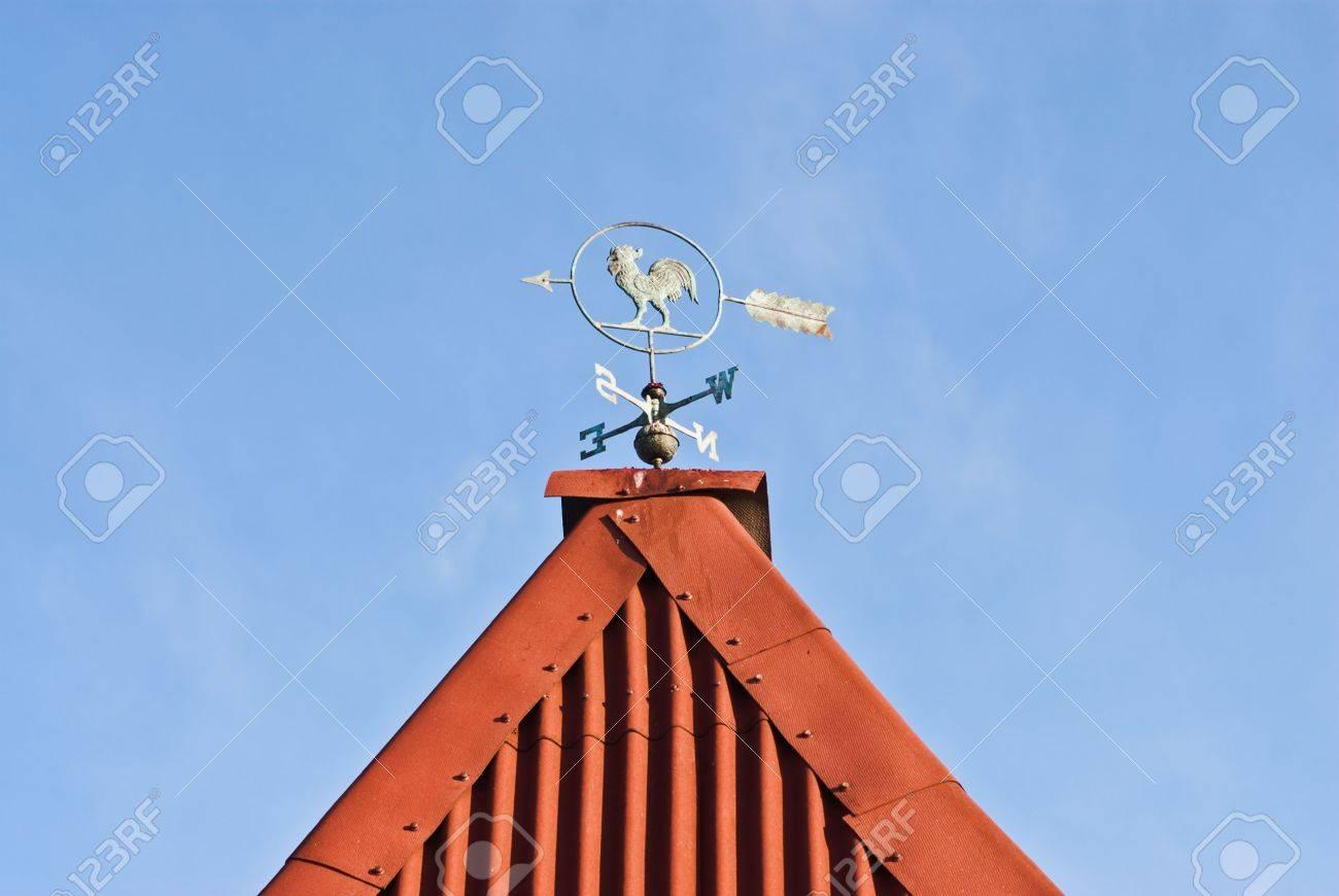 foto de archivo la veleta sobre el tejado de una casa de campo sobre un fondo de cielo azul