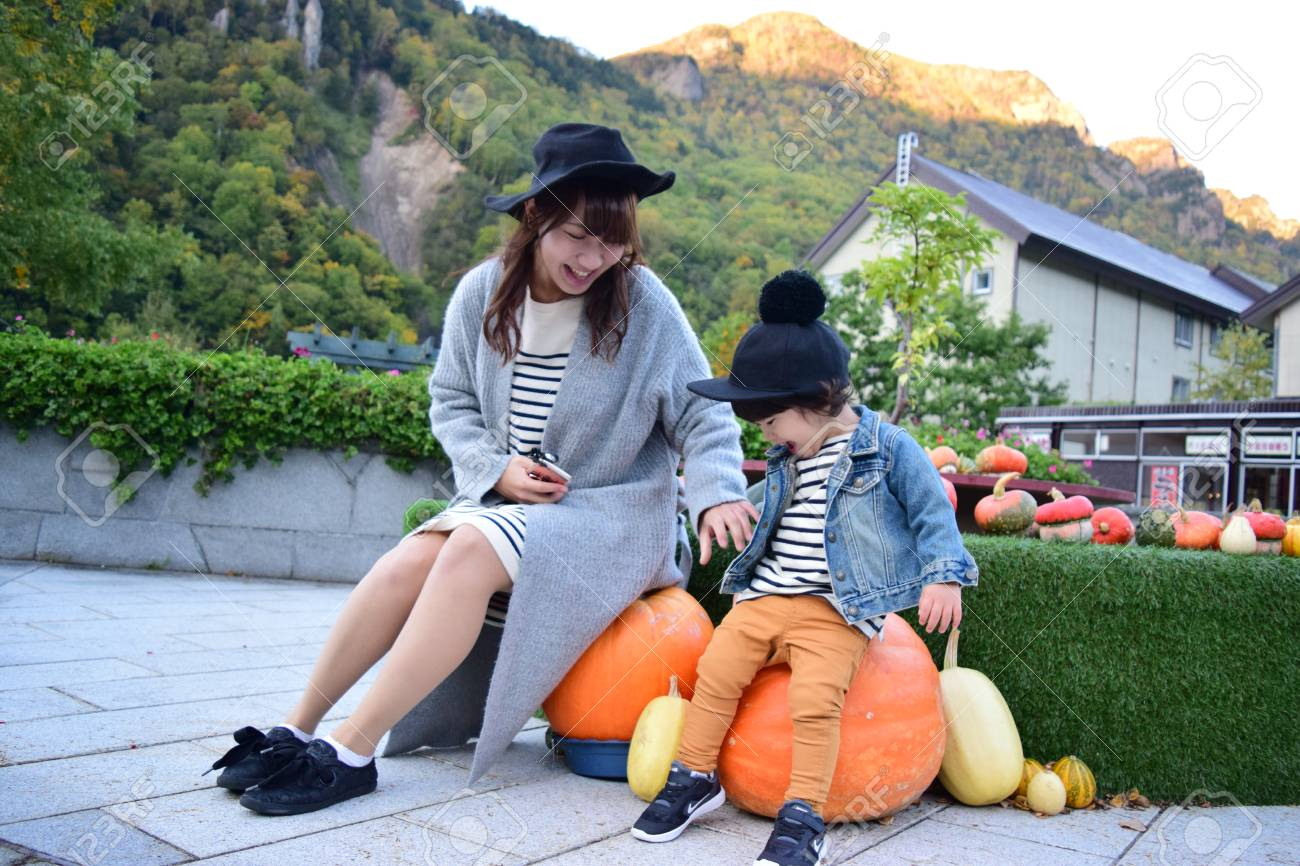 halloween mother and son with colorful pumpkin - 80200697