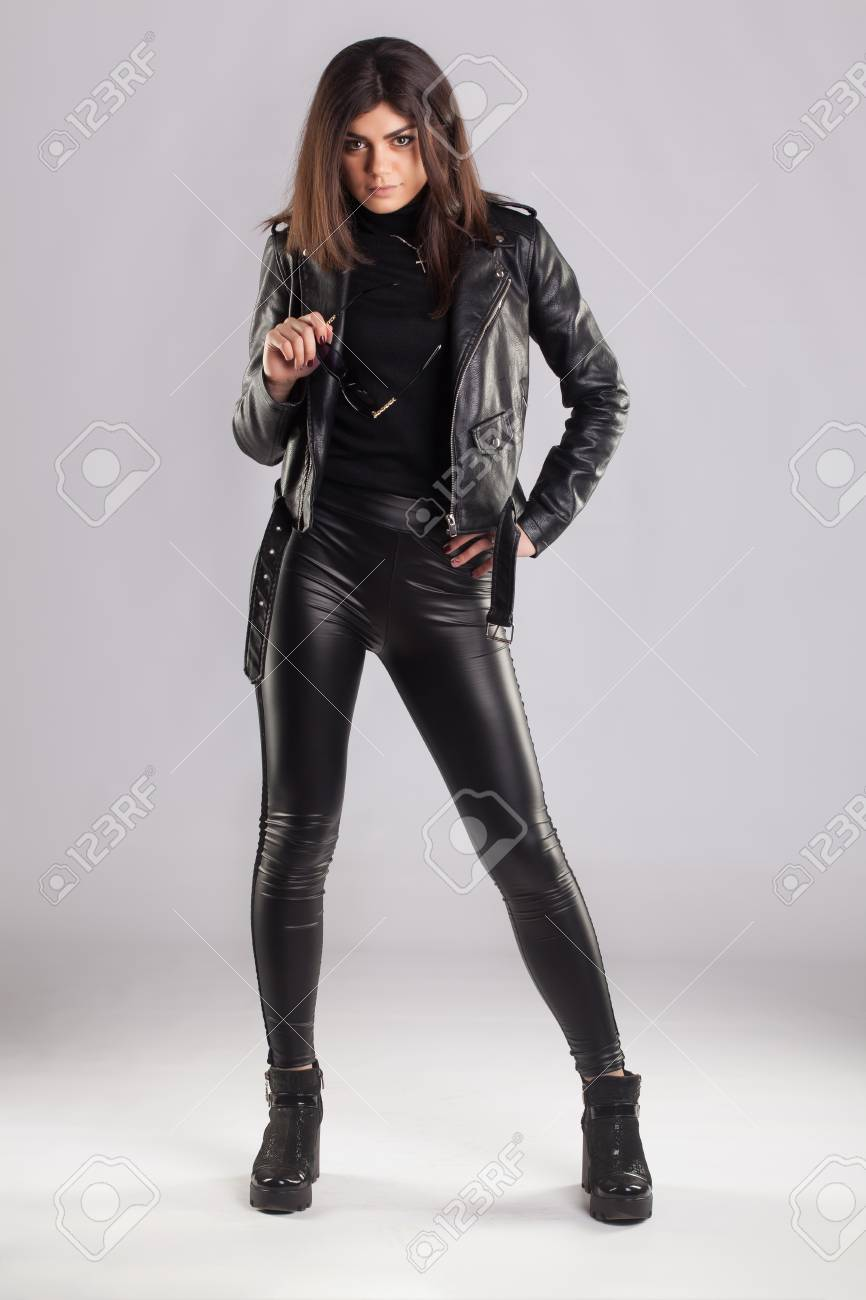 ef6ec19b5c7350 Stock Photo - Young brunette lady in black leather jacket and pants posing  on grey background