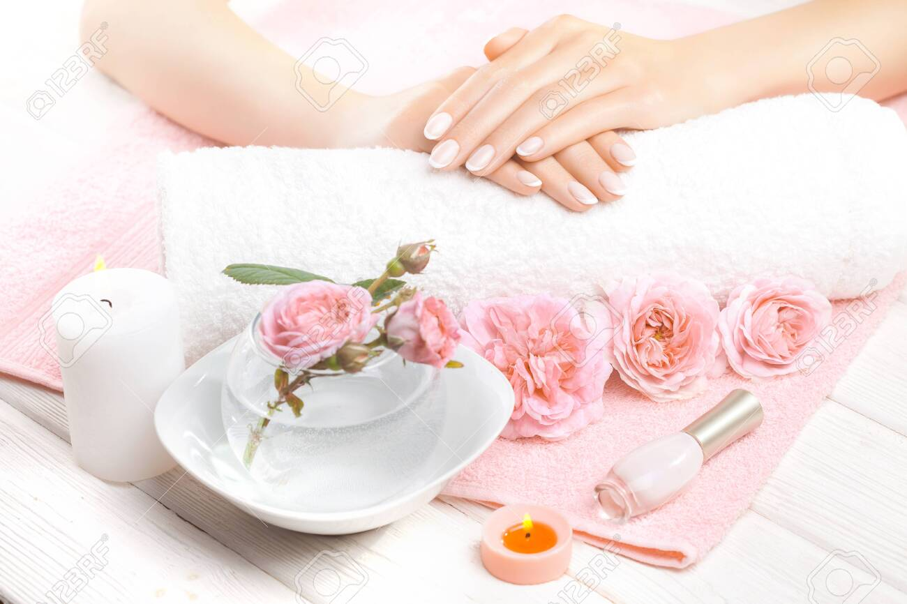 beautiful french manicure with roses, candle and towel on the white wooden table. - 149462851
