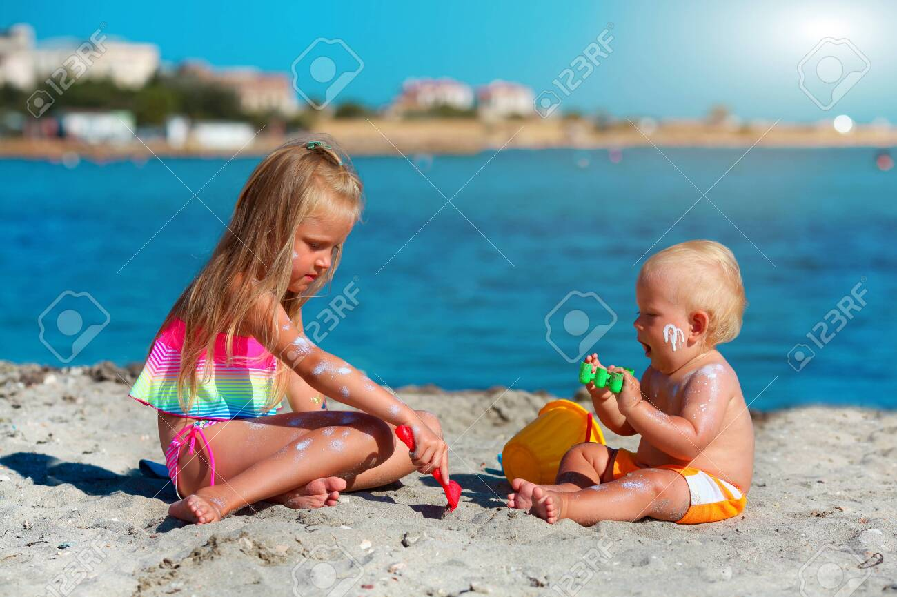 Children play on the beach. Summer water fun for the family. Boy and girl with toy buckets and a shovel on the seashore. Sunscreen applied to children is skin - 148612873