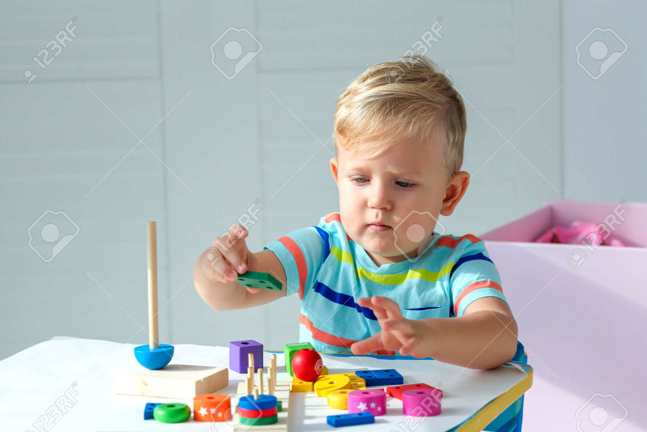 Little boy 2 years old is played with a wooden pyramid. Educational logic toys for children. Montessori games for child development. Copy space. - 158663191