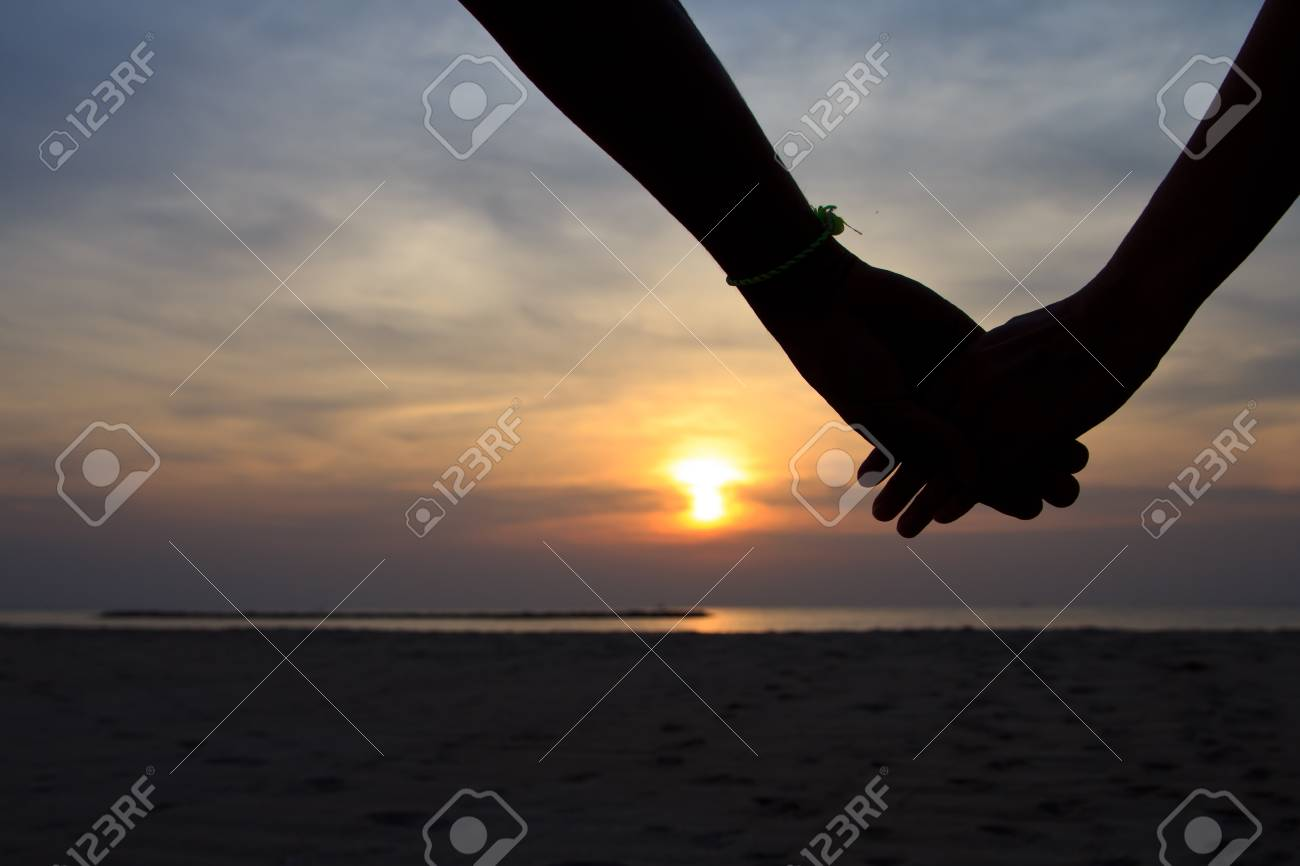 Silhouette hand in heart shape with sunrise in the middle and beach background Stock Photo - 17876786