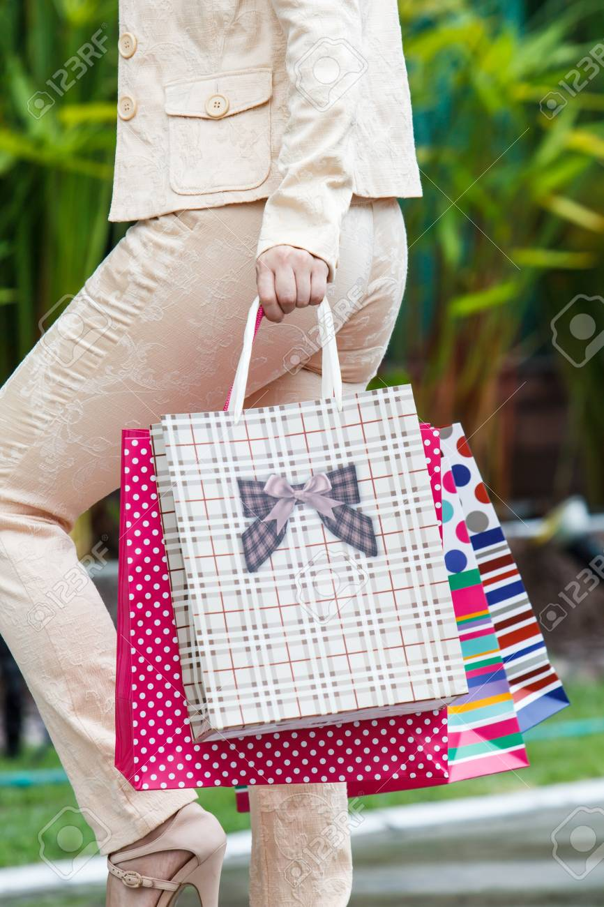 Young trendy girl holding up shopping bag Stock Photo - 20822558