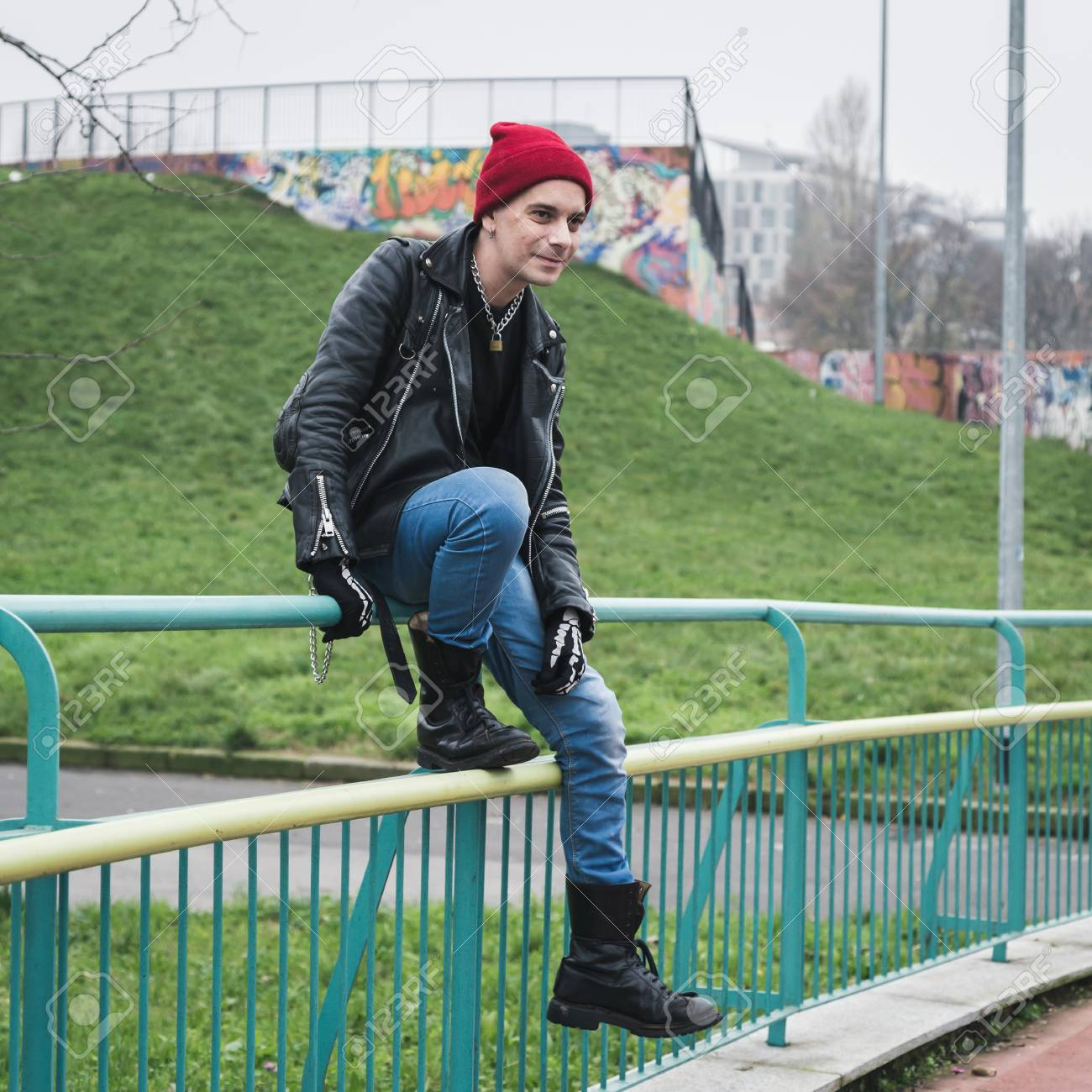 28a93a843d2 Punk guy with beanie posing in a city park Stock Photo - 34600757