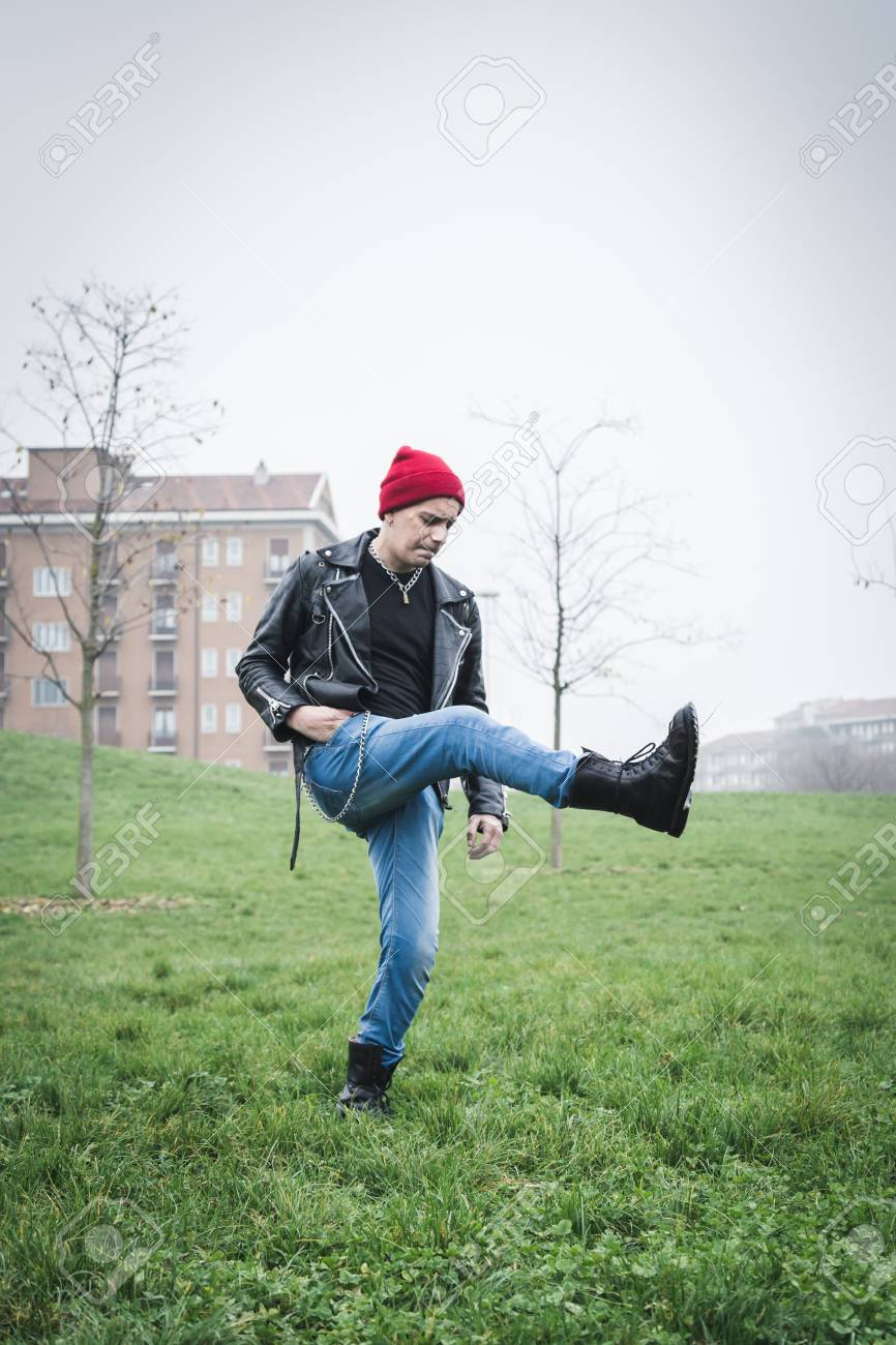 08b8e6d53a9 Punk guy with beanie posing in a city park Stock Photo - 34600759