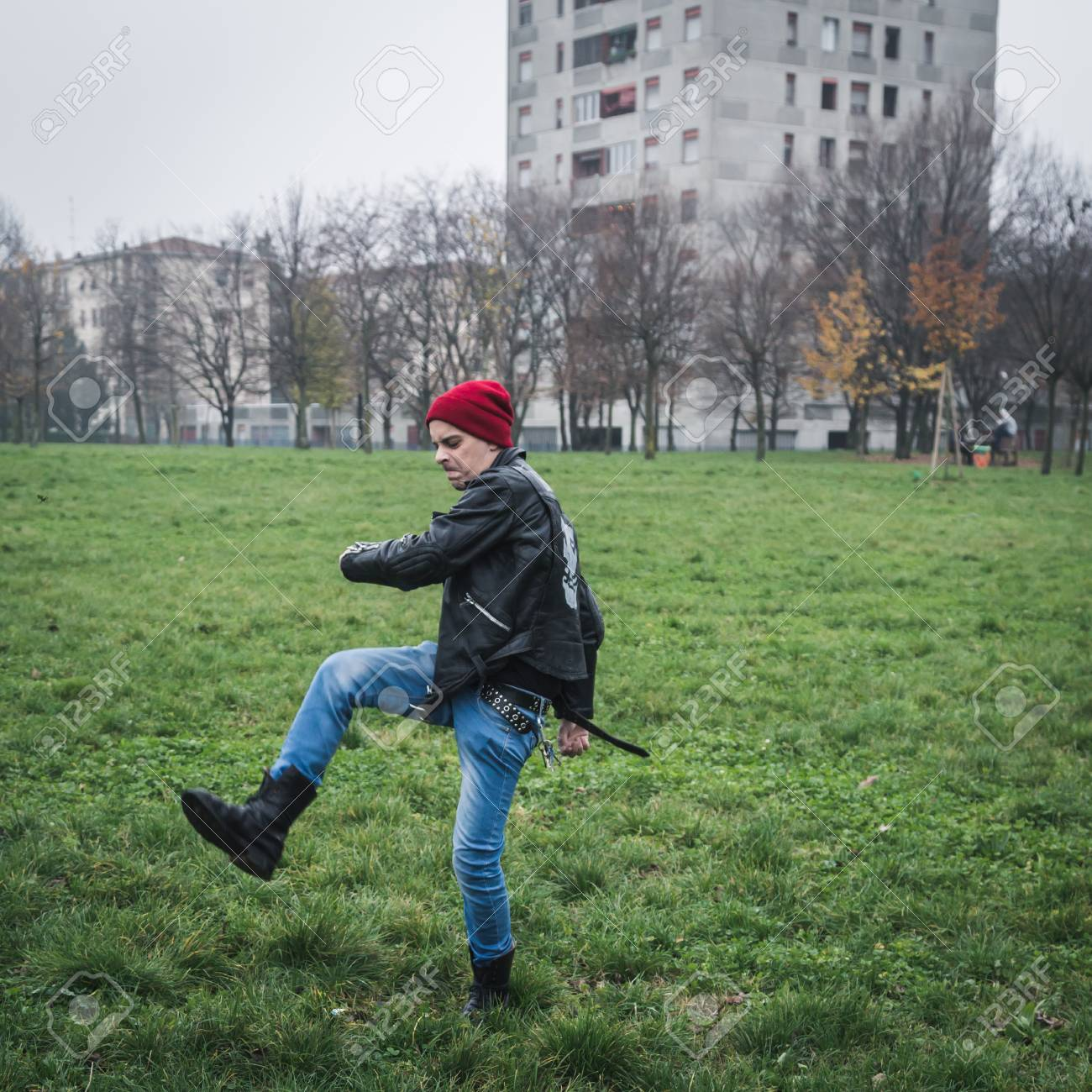 d2ddae7ea8d Punk guy with beanie posing in a city park Stock Photo - 34600760