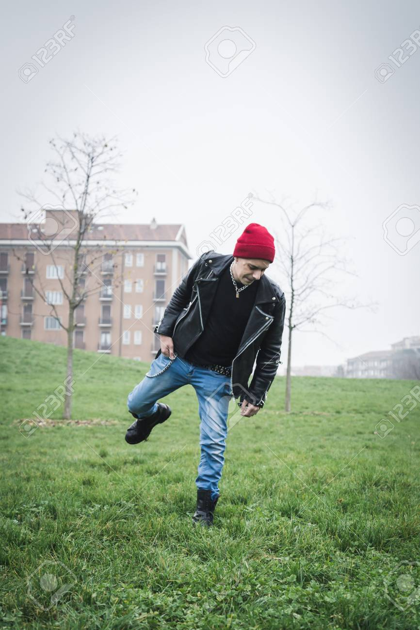 04938aa9bf1 Punk guy with beanie posing in a city park Stock Photo - 34600894