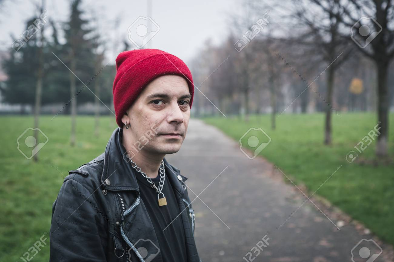 c05537d31bd Punk guy with beanie posing in a city park Stock Photo - 34600896