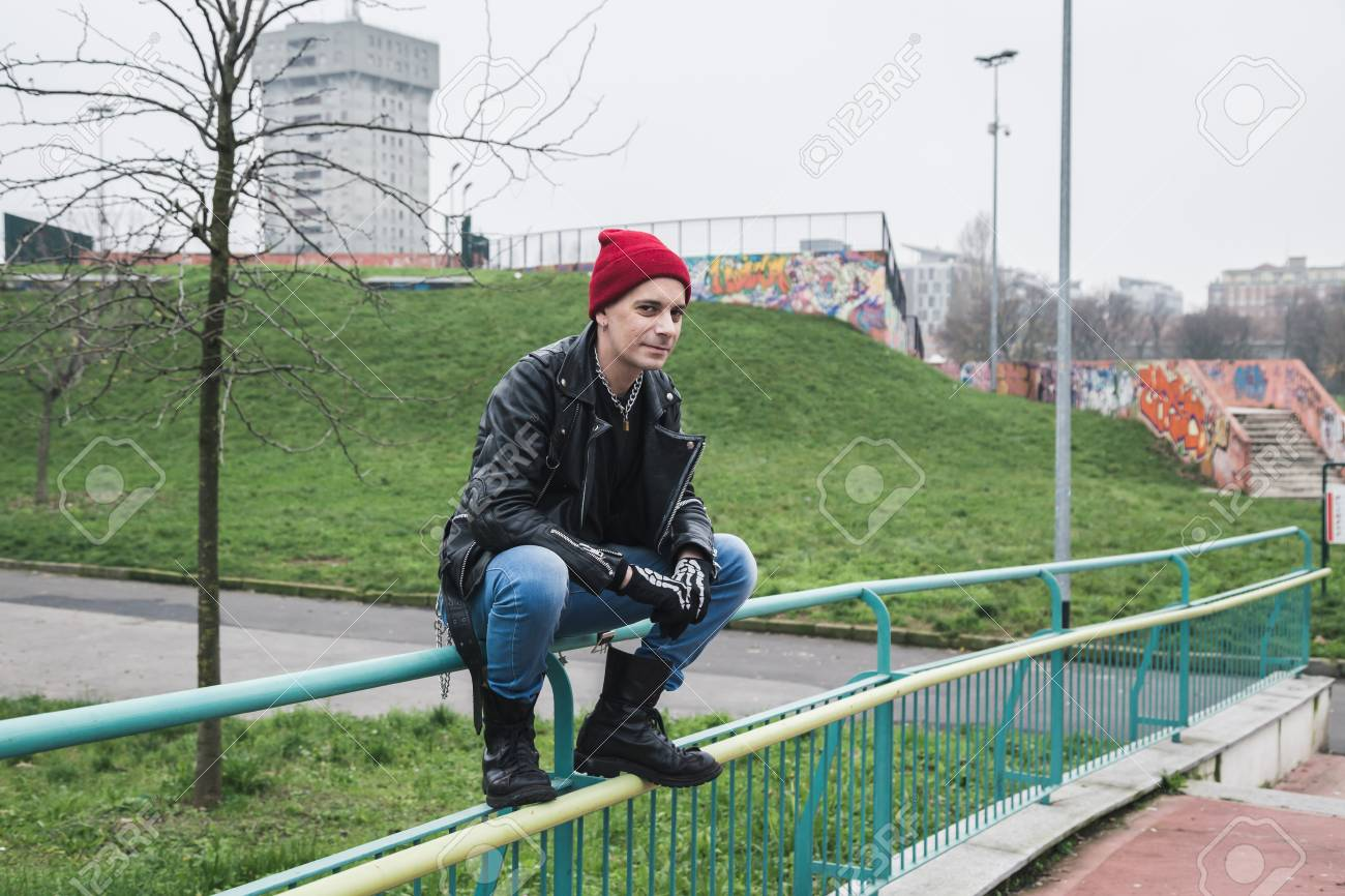 a010623a7e8 Punk guy with beanie posing in a city park Stock Photo - 35361664