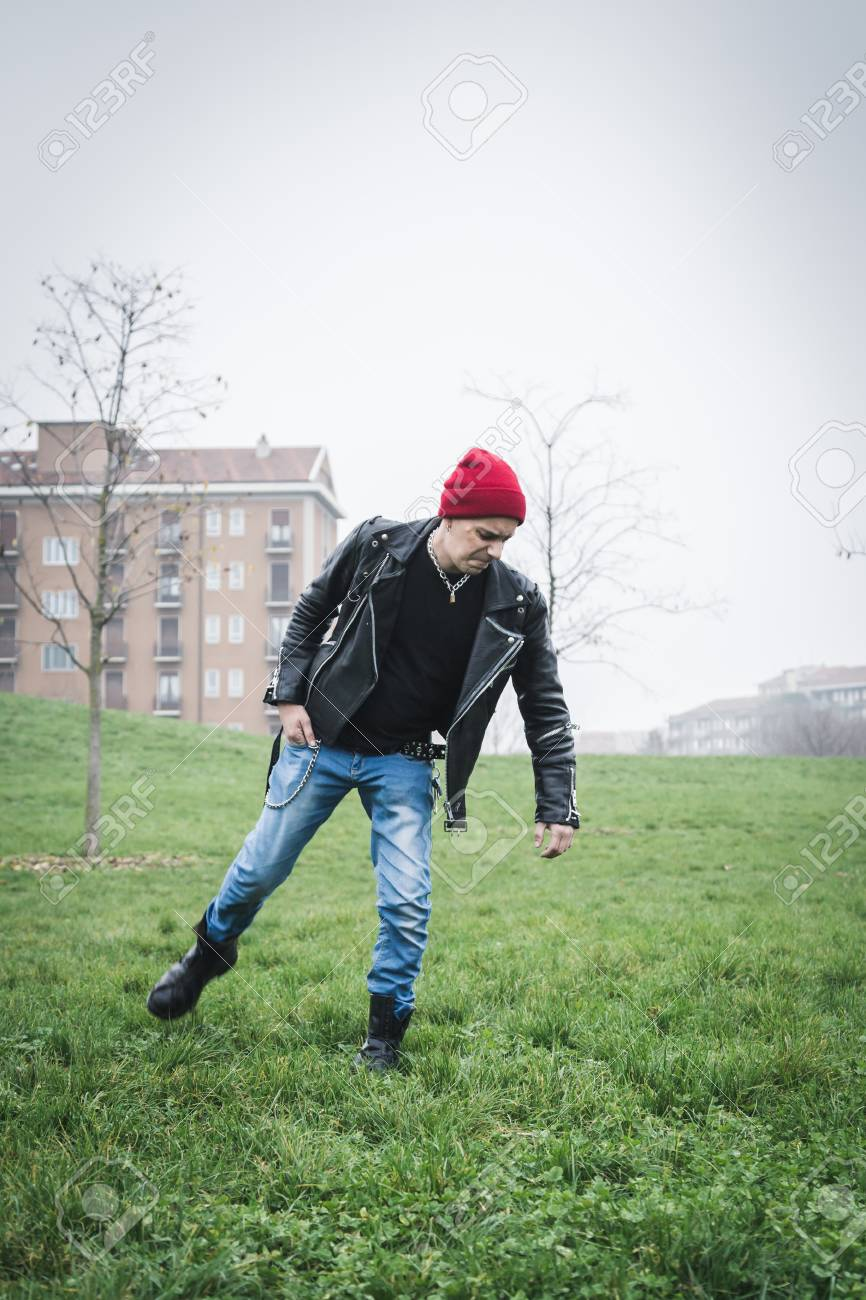 21a722e17b7 Punk guy with beanie posing in a city park Stock Photo - 35361672