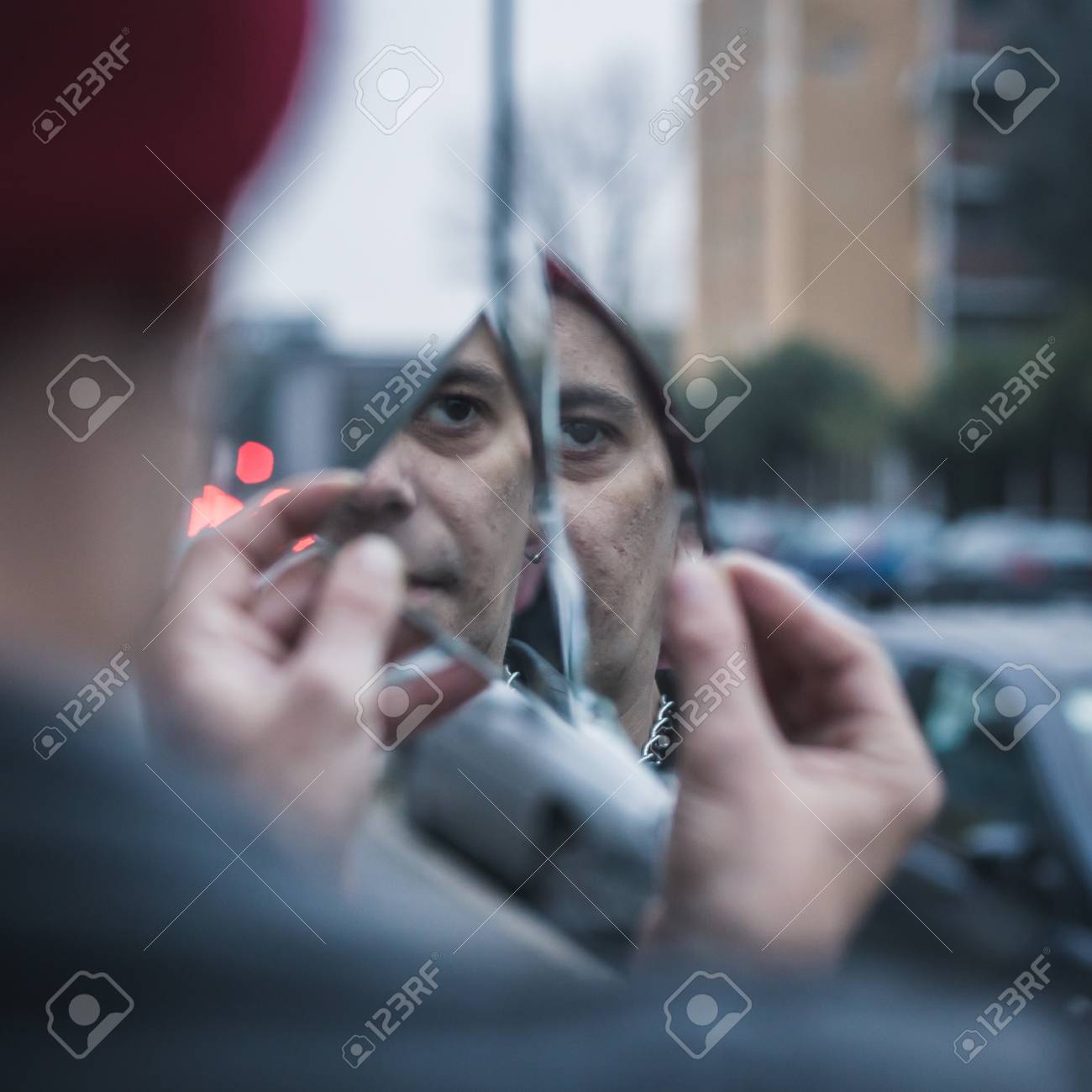 203f719c3b0 Punk guy looking at himself in a shattered mirror in the city streets Stock  Photo -