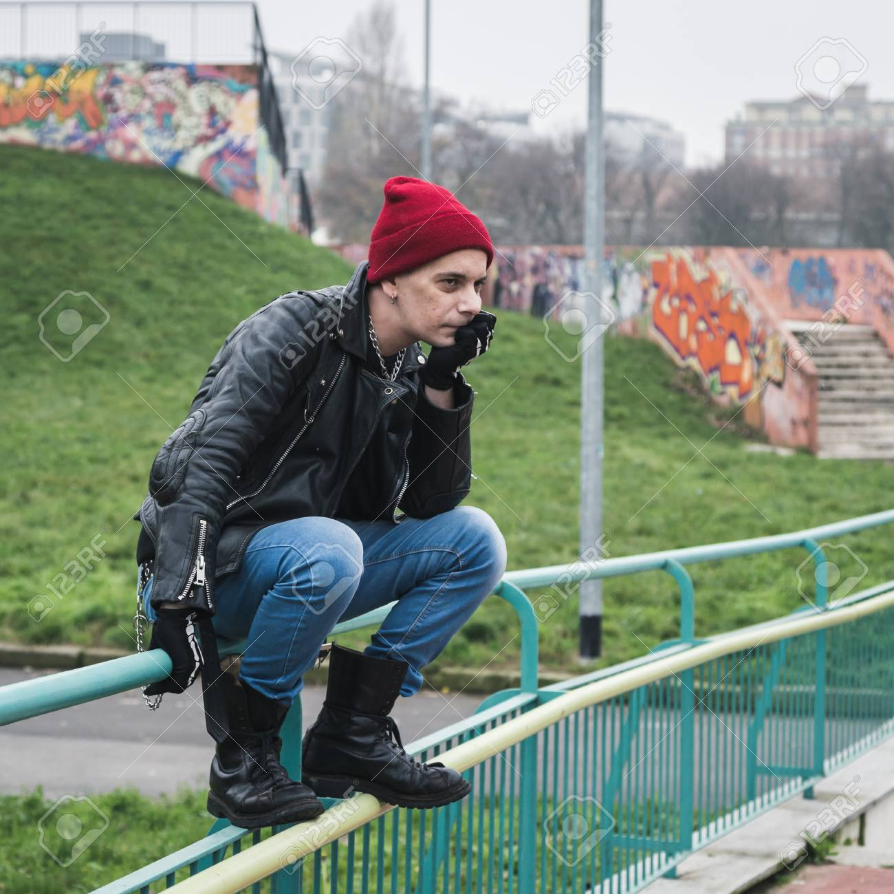 fe597aea5bf Punk guy with beanie posing in a city park Stock Photo - 36177664