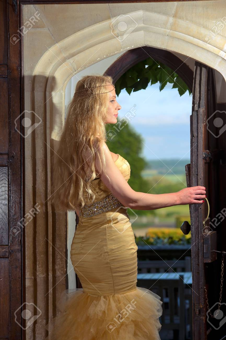 Beautiful blonde woman in luxurious interior room looking outside Stock Photo - 20573792