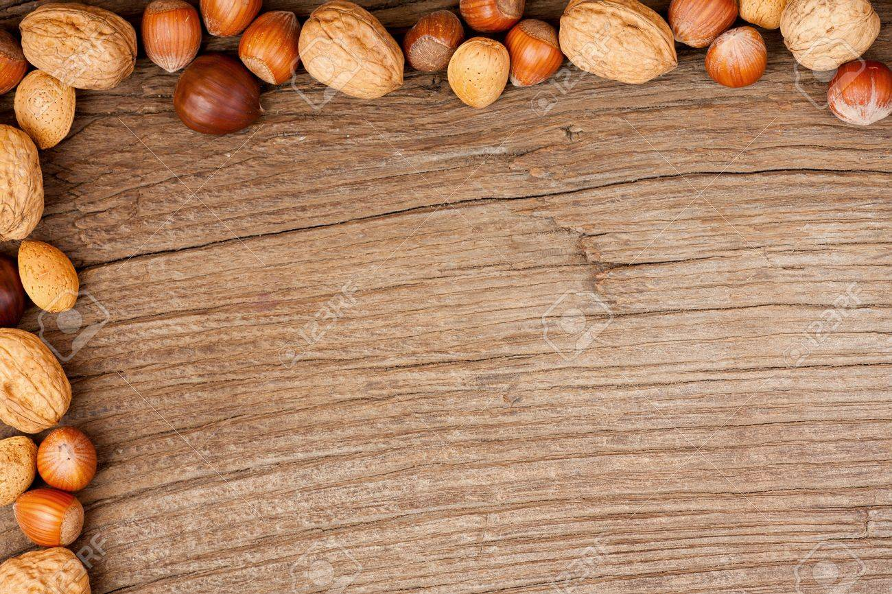 Decorated background of old wooden plate with different types of nuts on two sides Stock Photo - 20239564