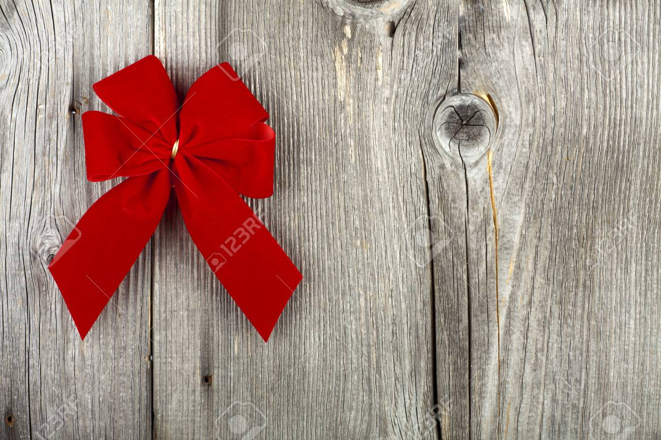 Christmas Greeting with a red Ribbon Bow on old wooden Board and Copy Space on the right Image side Stock Photo - 23483215