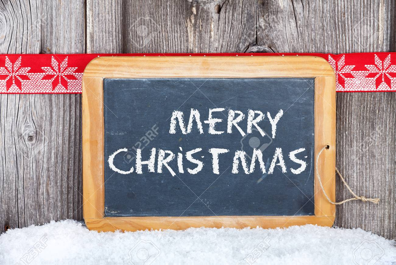 Christmas Greetings old Slate Chalkboard with Words  Merry Christmas  on old wooden Board Stock Photo - 23483219