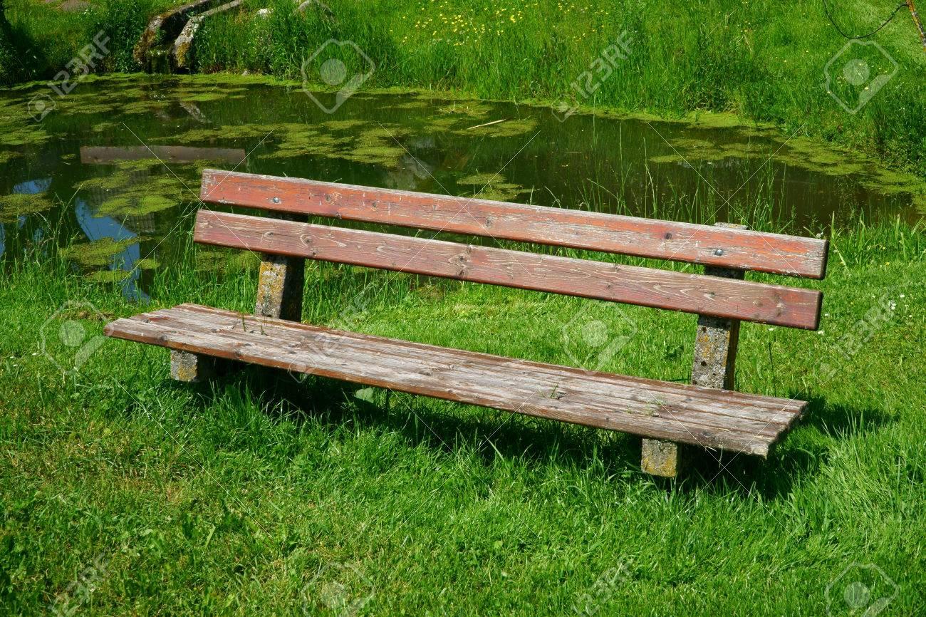 Ancien Siège De Banc De Bois Dans Le Jardin Avec Un étang En Arrière