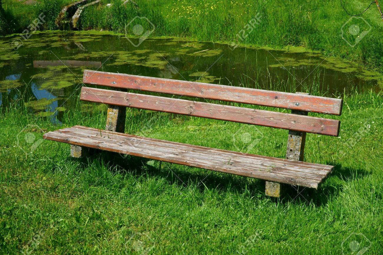 Old Wooden Bench Seat In The Garden With A Pond In The Background