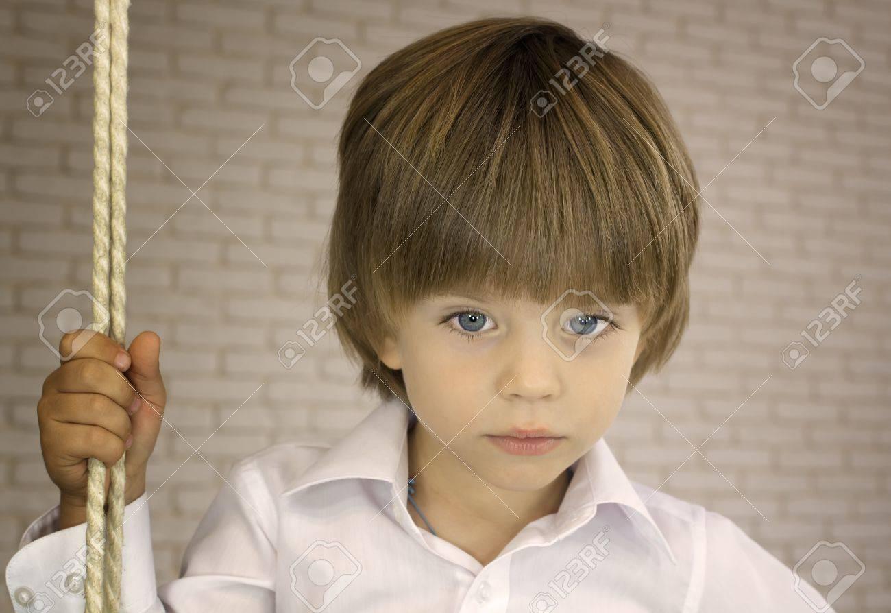 青い目の少年が縄と白いシャツで...