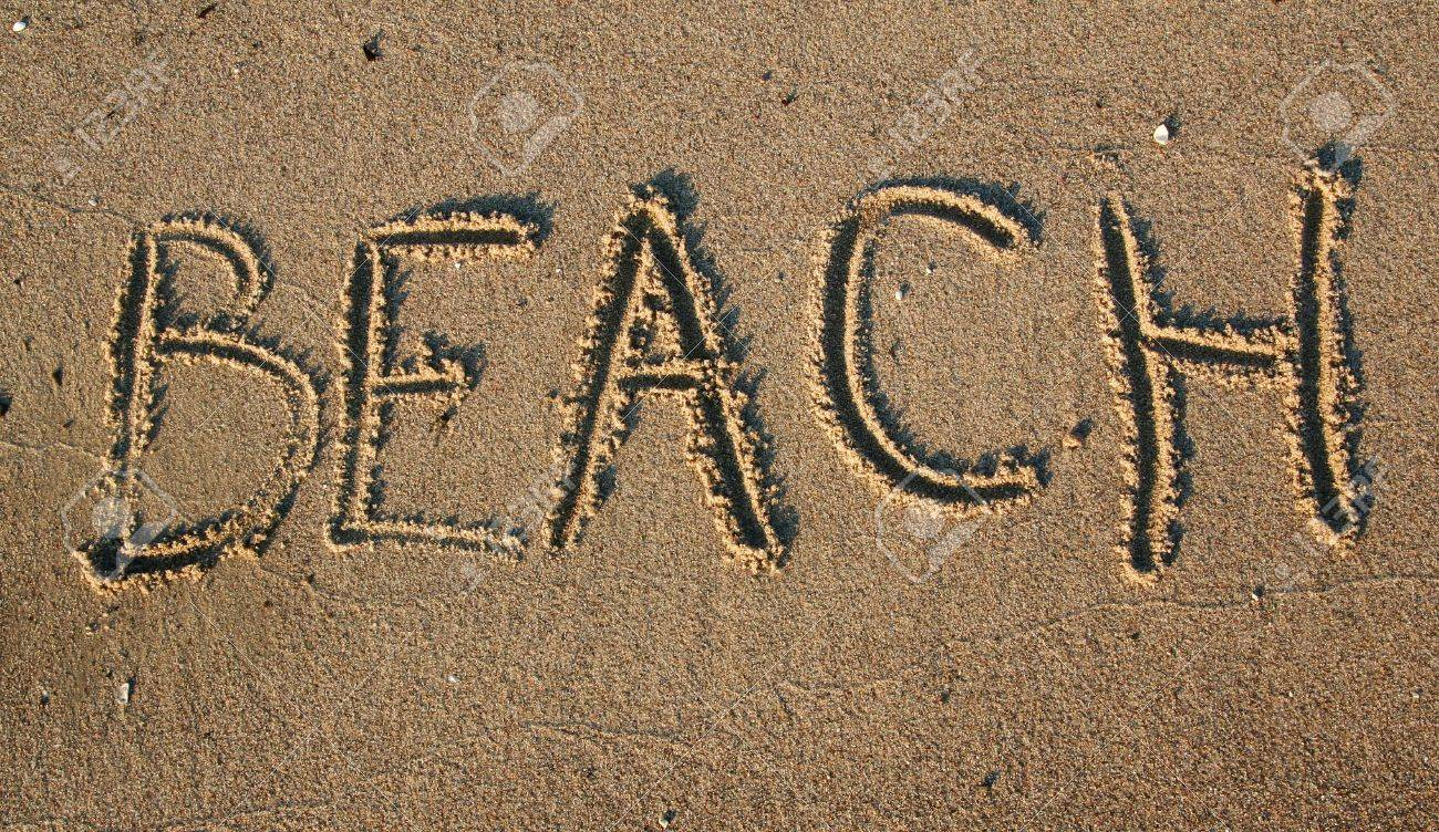stock photo writting in the sand on beach message saying beach in capital letters