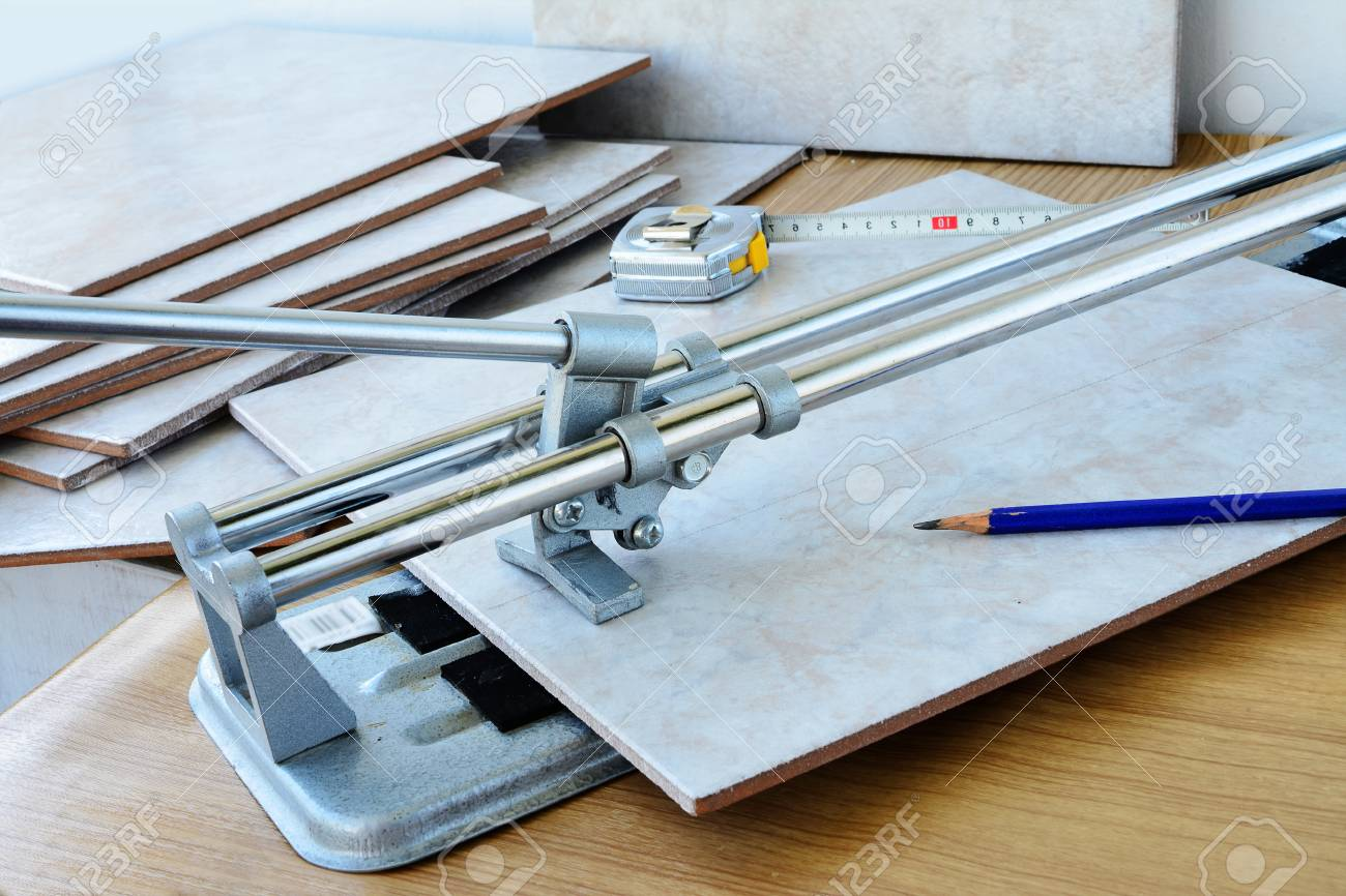Cutting ceramic tiles with manual tile cutter machine, DIY home