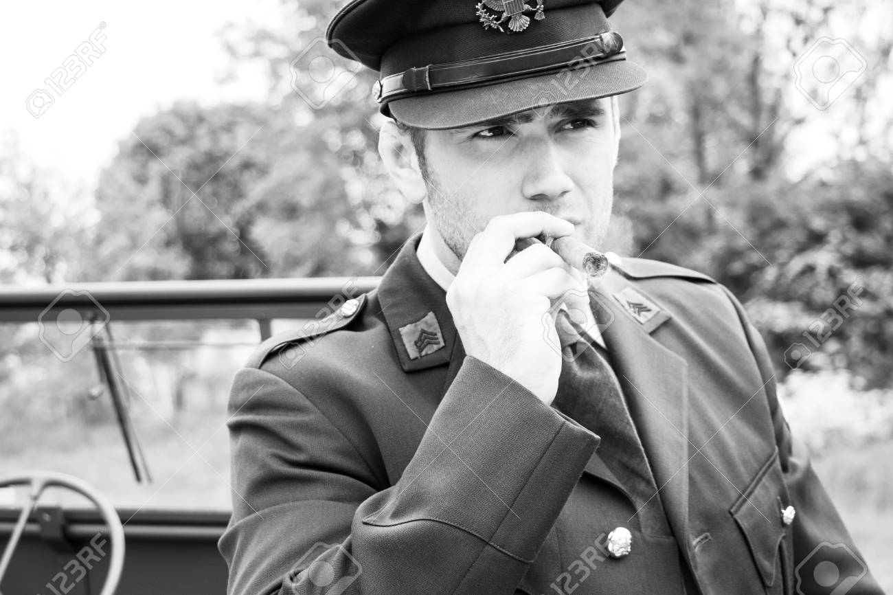 Handsome American WWII GI Army officer in uniform smoking cigar