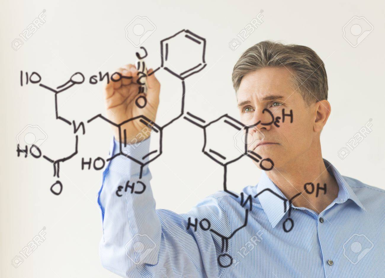 Mature male scientist drawing molecular structure on transparent board against white wall Stock Photo - 22079305