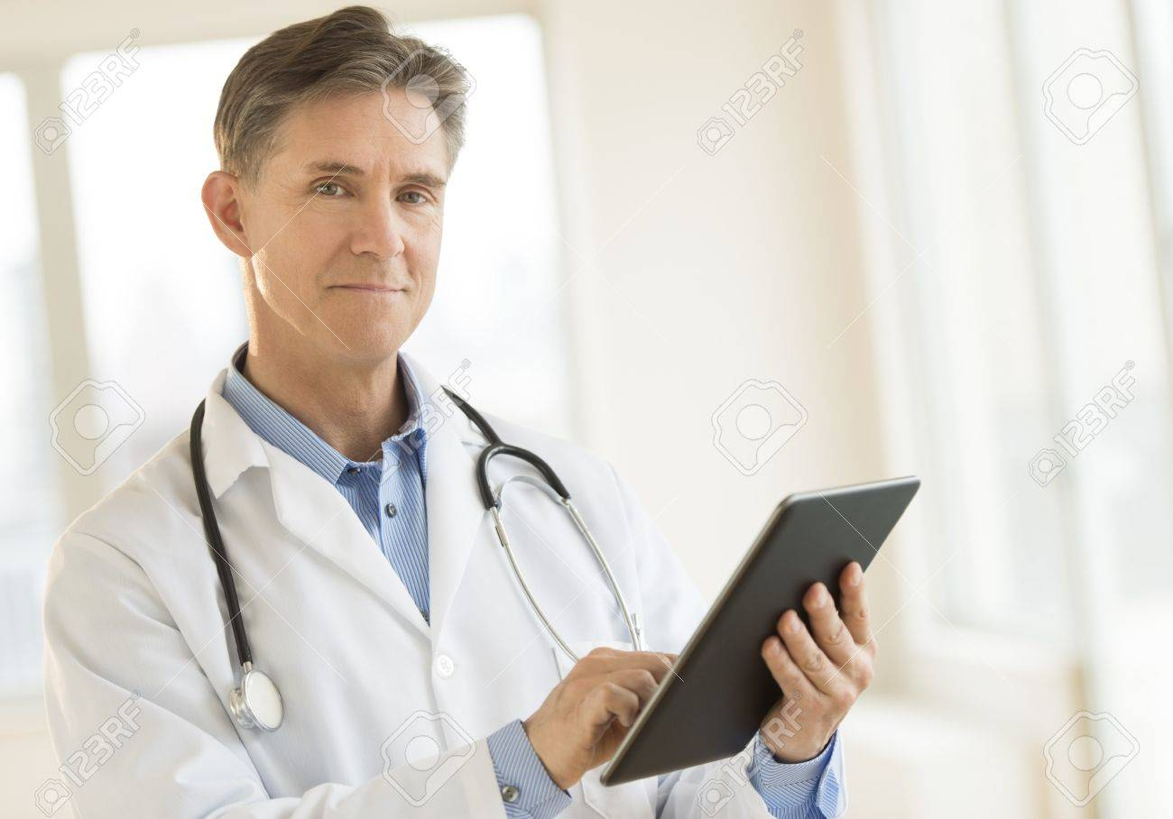 portrait of confident mature male doctor holding digital tablet
