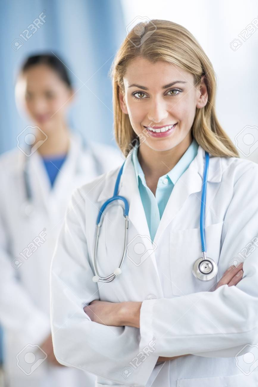 Portrait of happy young female doctor standing arms crossed at clinic with colleague in background Stock Photo - 22143627