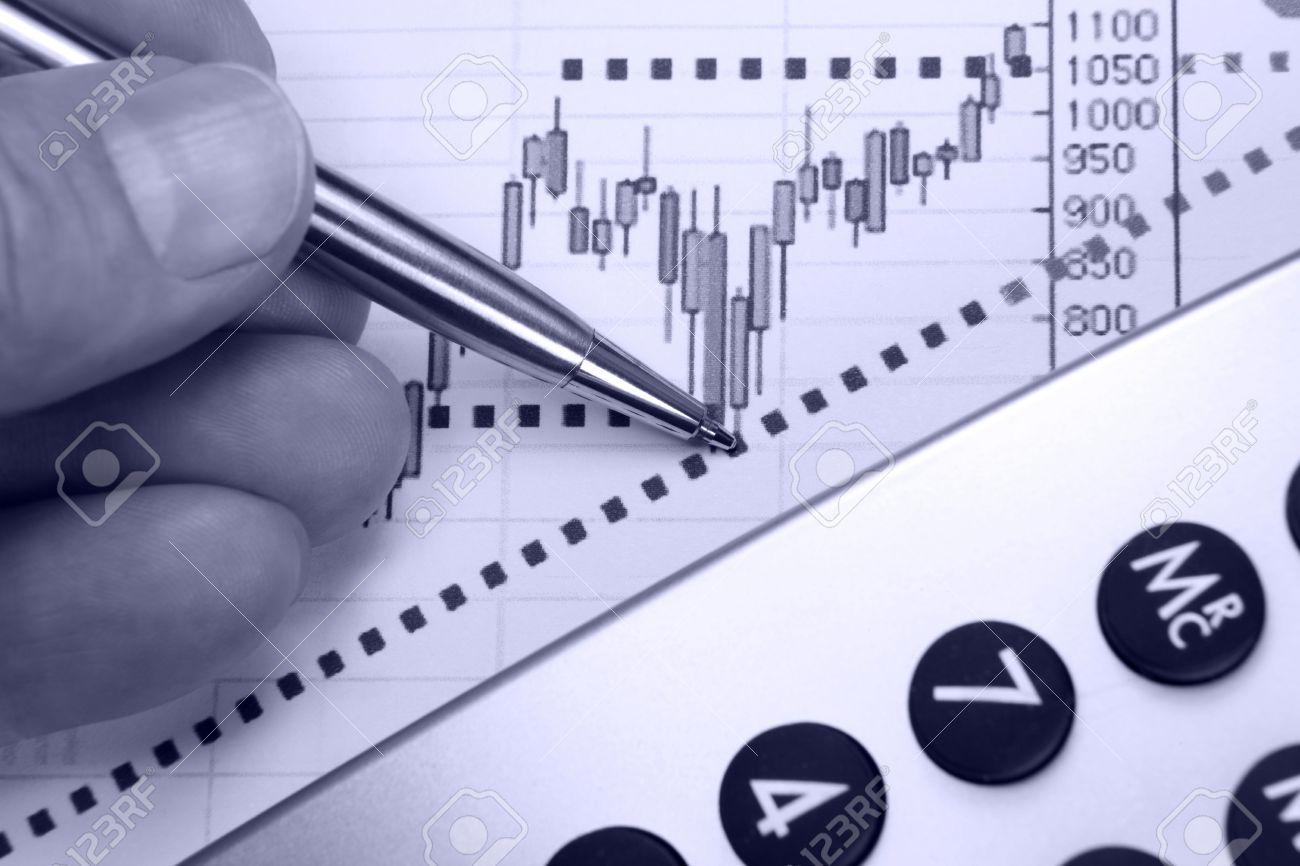 Financial chart, market's rising, calculator, pen, human hand, focus on chart at pen tip. Stock Photo - 6731677