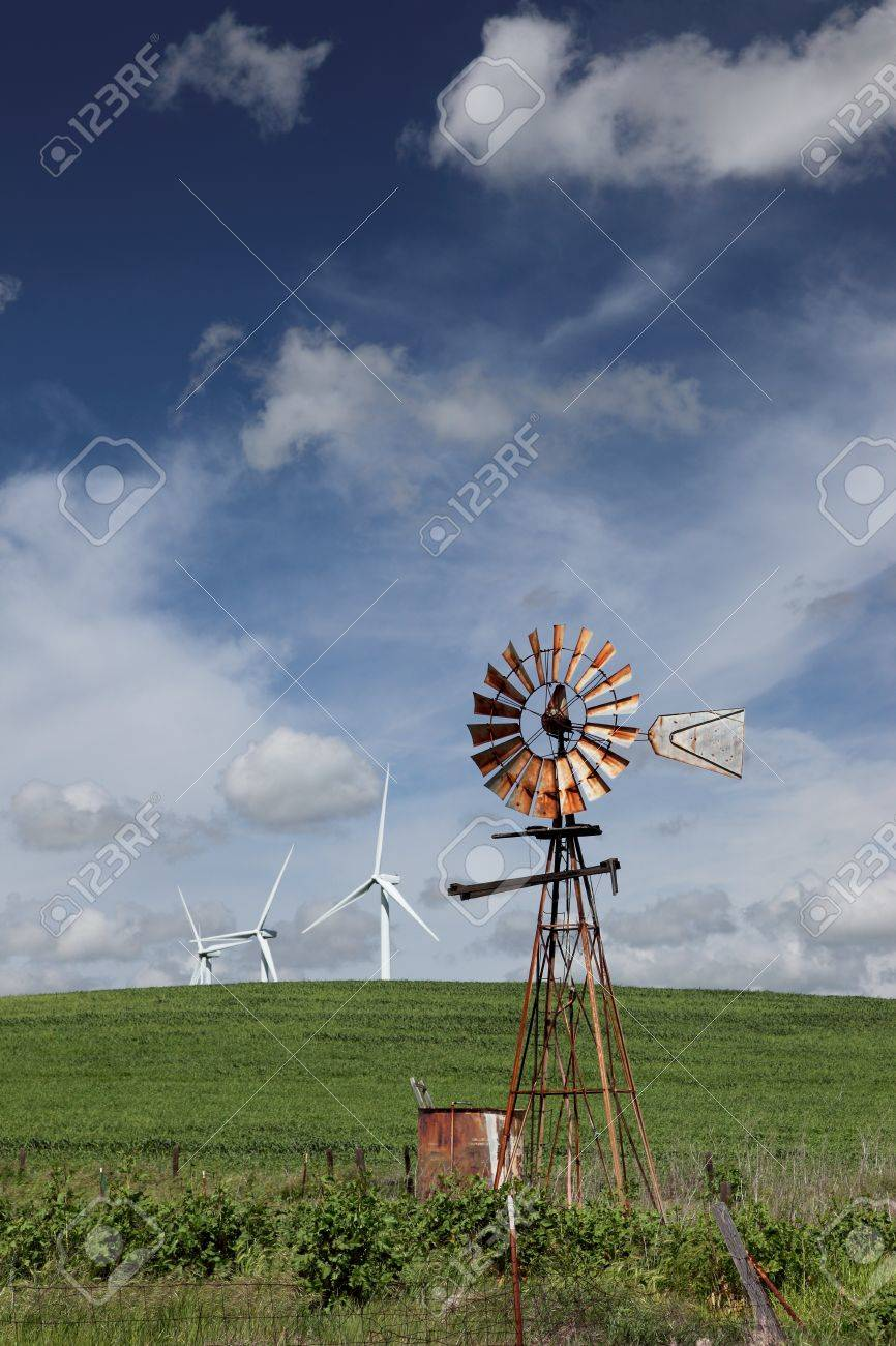 Old ranch windmill and white power generating wind turbines, against dramatic clouds, blue sky, on agricultural green wheat fields. Stock Photo - 7025219