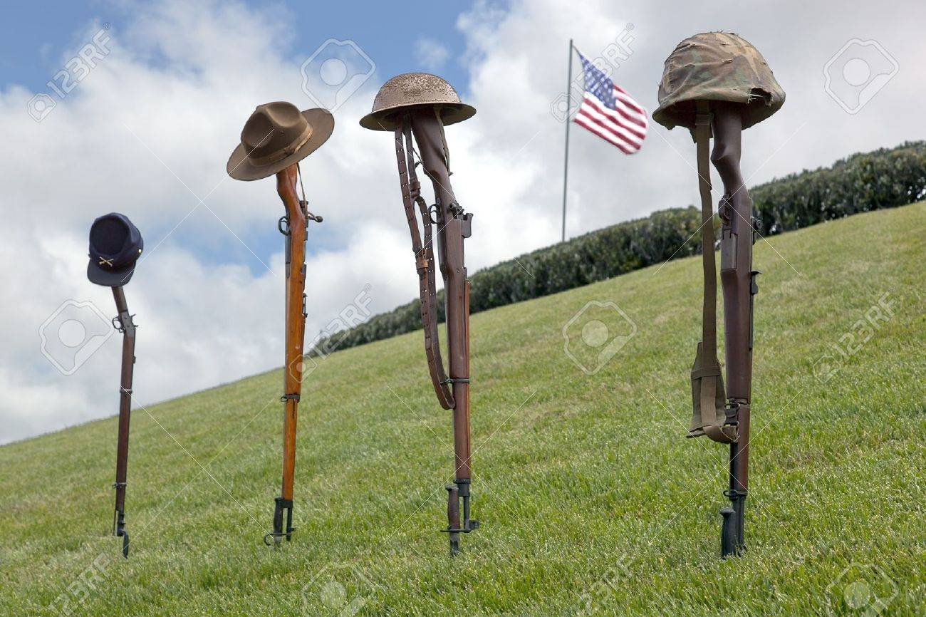 Vintage riflles and soldier's hats and helmets forming Fallen Soldier Battle Crosses, American Flag behind. Stock Photo - 14629247