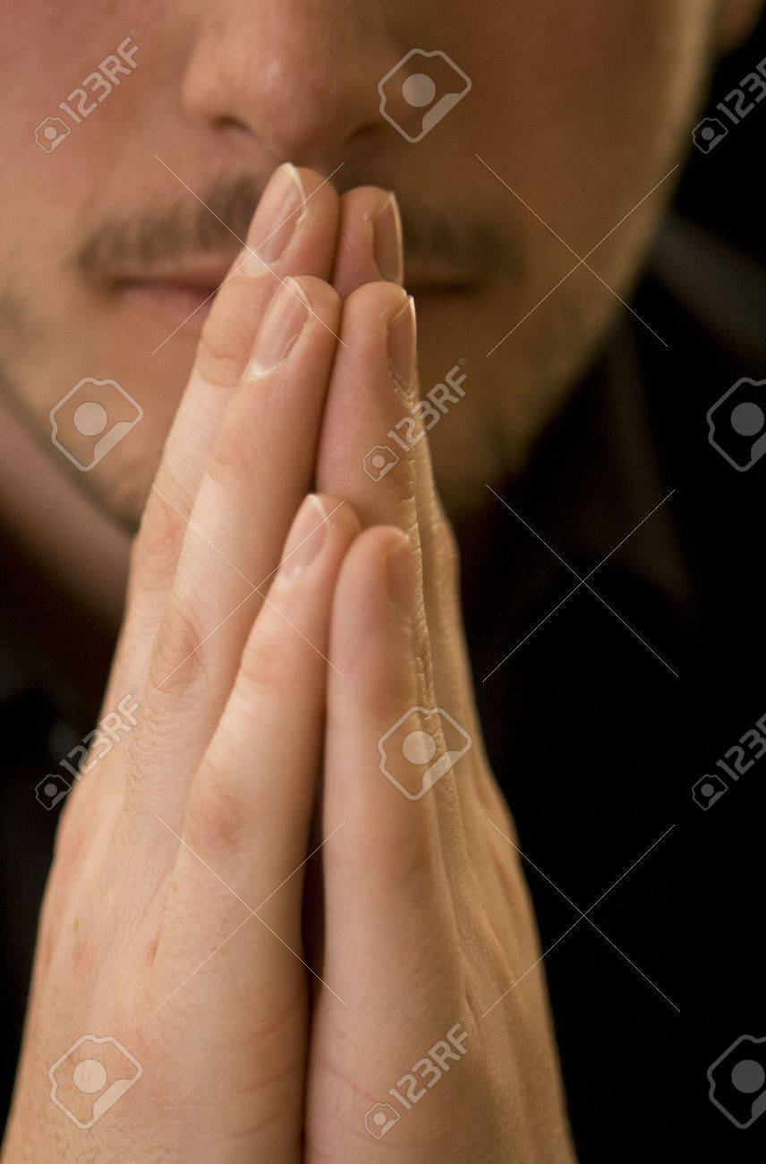 Man's hands together in prayer with just his mouth and nose visible in the background. Gold reflector used to warm the lighting. Stock Photo - 4209276
