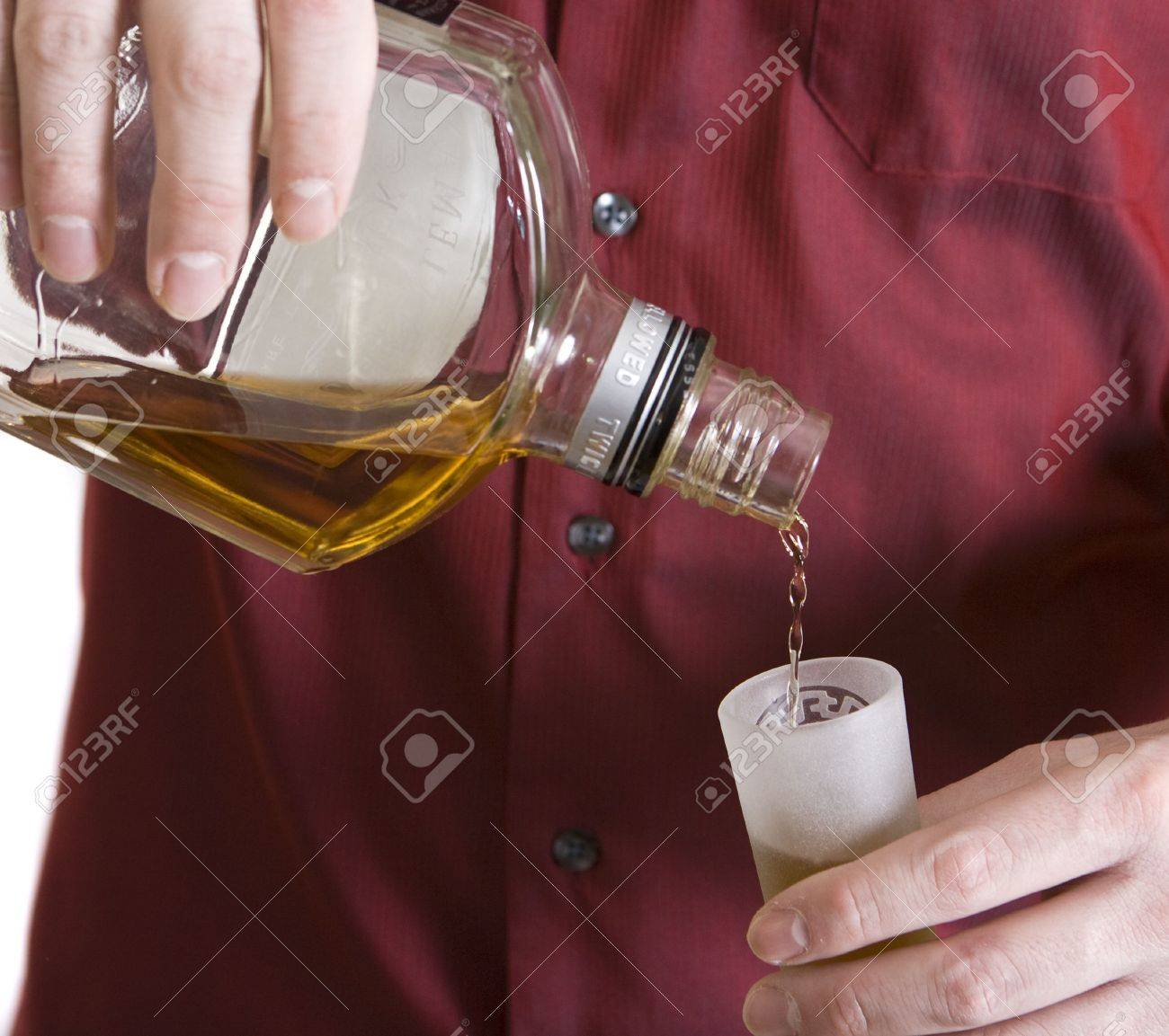 Man's hands pouring whiskey into a shot glass. Stock Photo - 4245687