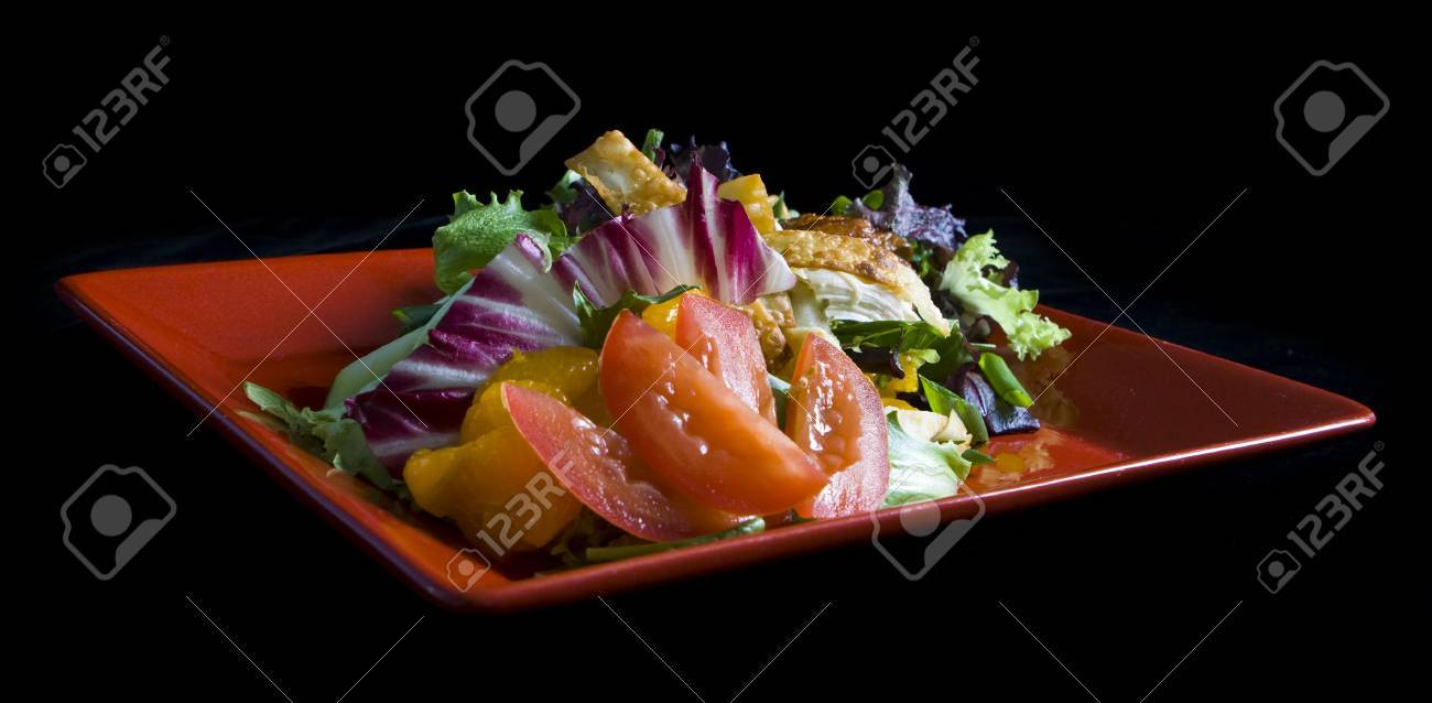 Gourmet chicken salad on red plate with black background Stock Photo - 4293621