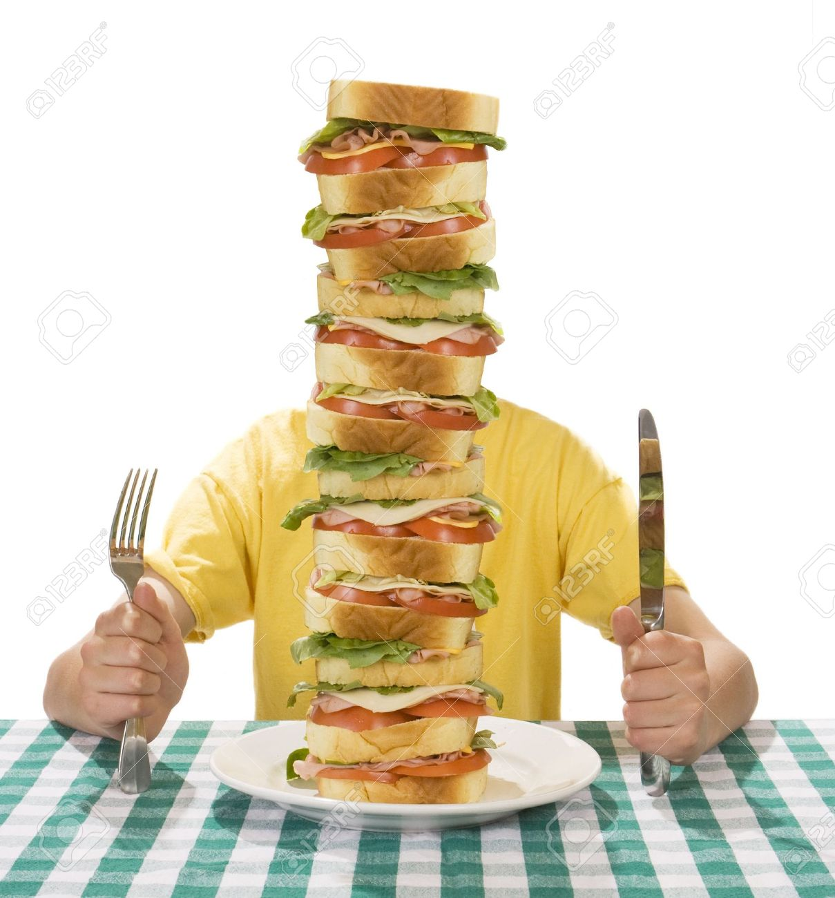Giant sandwich on a white plate, with hands holding a a knife and fork on a table cloth. Stock Photo - 4759346