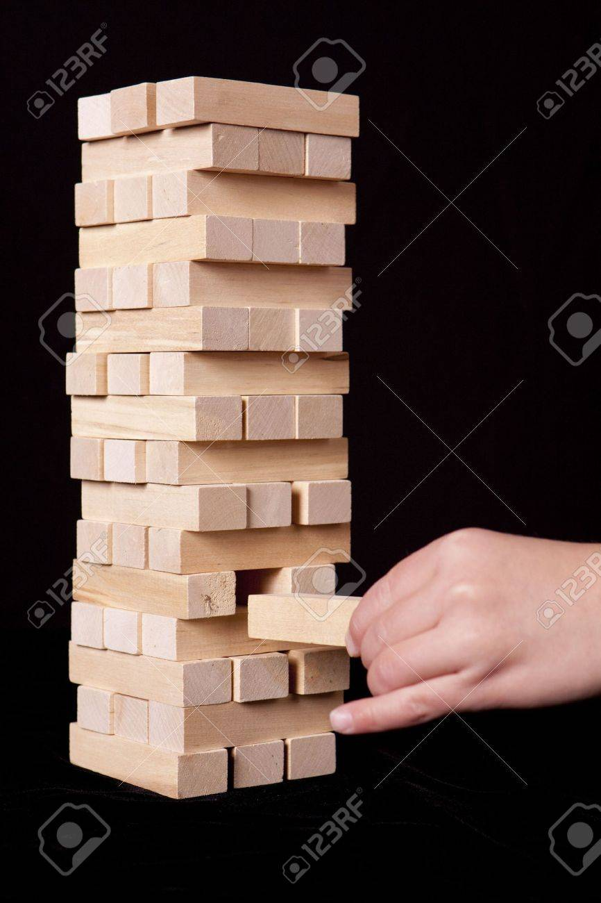 Stacked blocks against a black background with a child's hand removing one. Stock Photo - 6015804