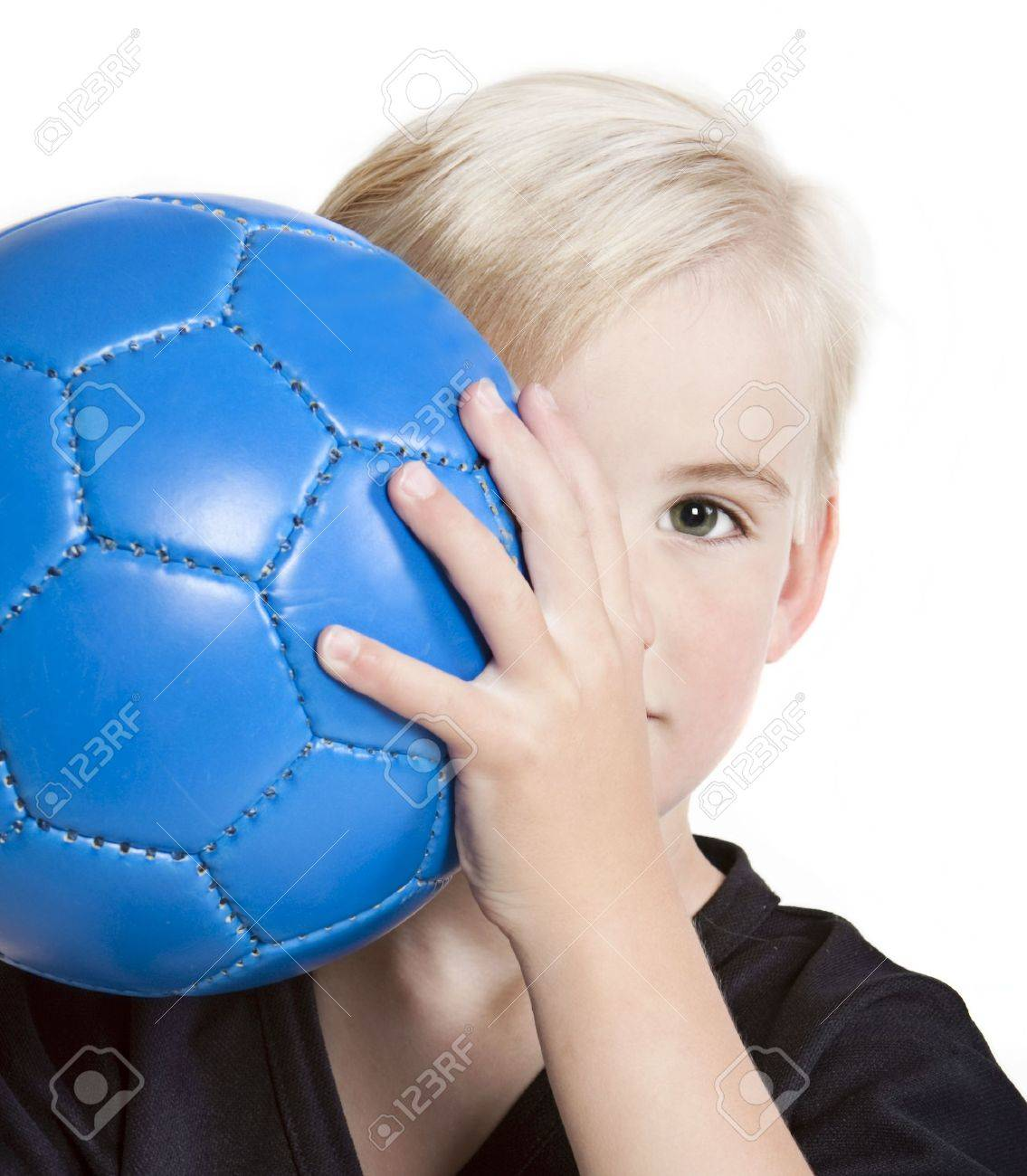 Young (preschool age) boy with blue soccer ball partially hidden behind face. Stock Photo - 7230204