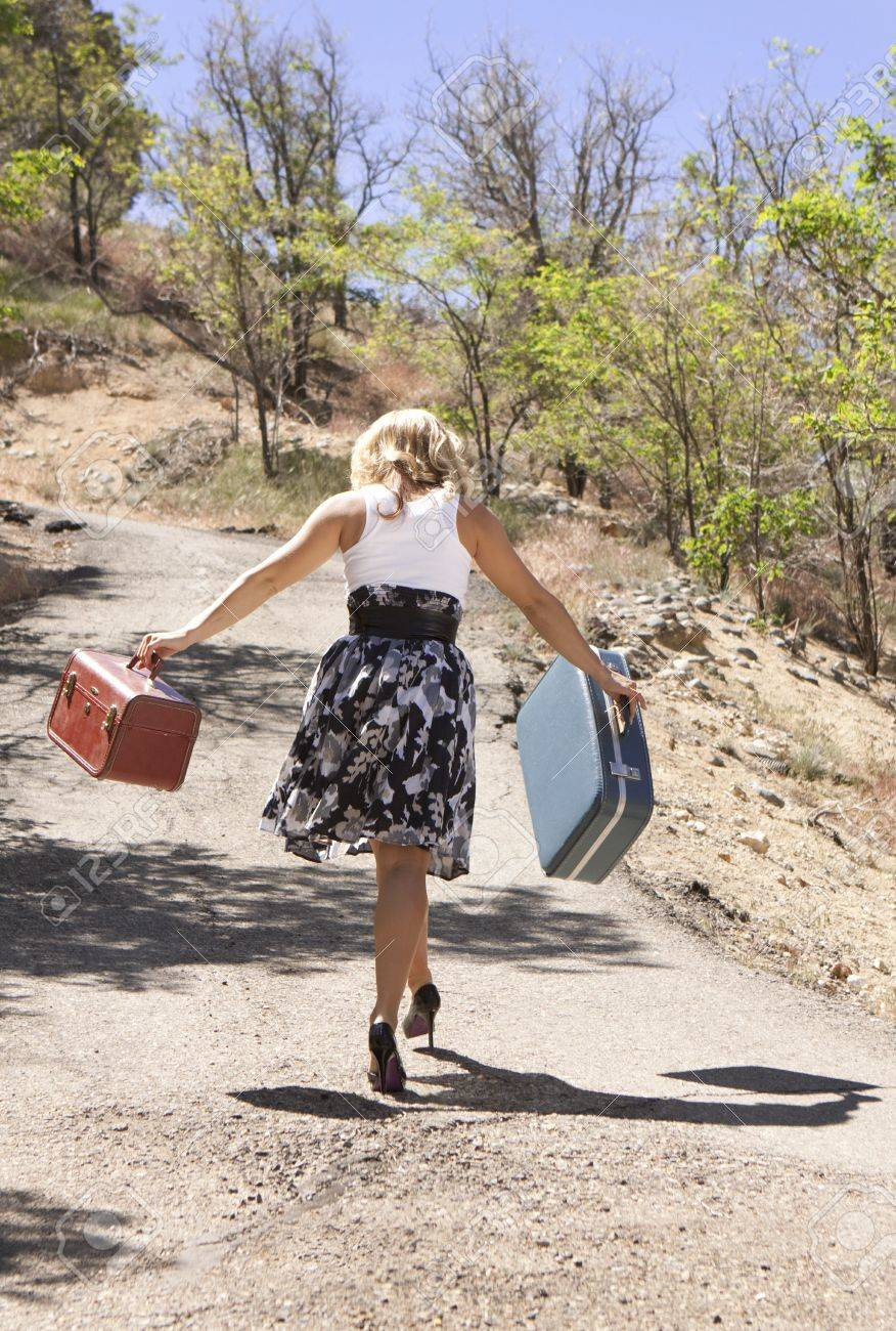 Girl walking down road carrying suitcases. Stock Photo - 7258229