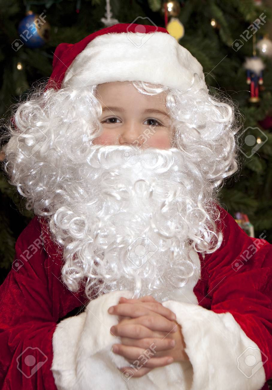 Young boy in front of Christmas tree wearing a Santa Claus suit. Stock Photo - 8420947