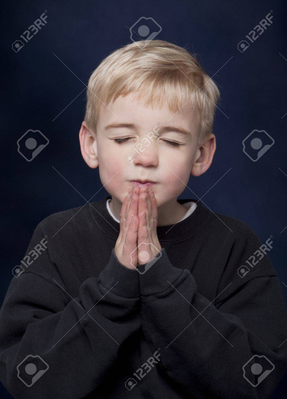 Young blond boy with his hands together in prayer. Stock Photo - 8754651