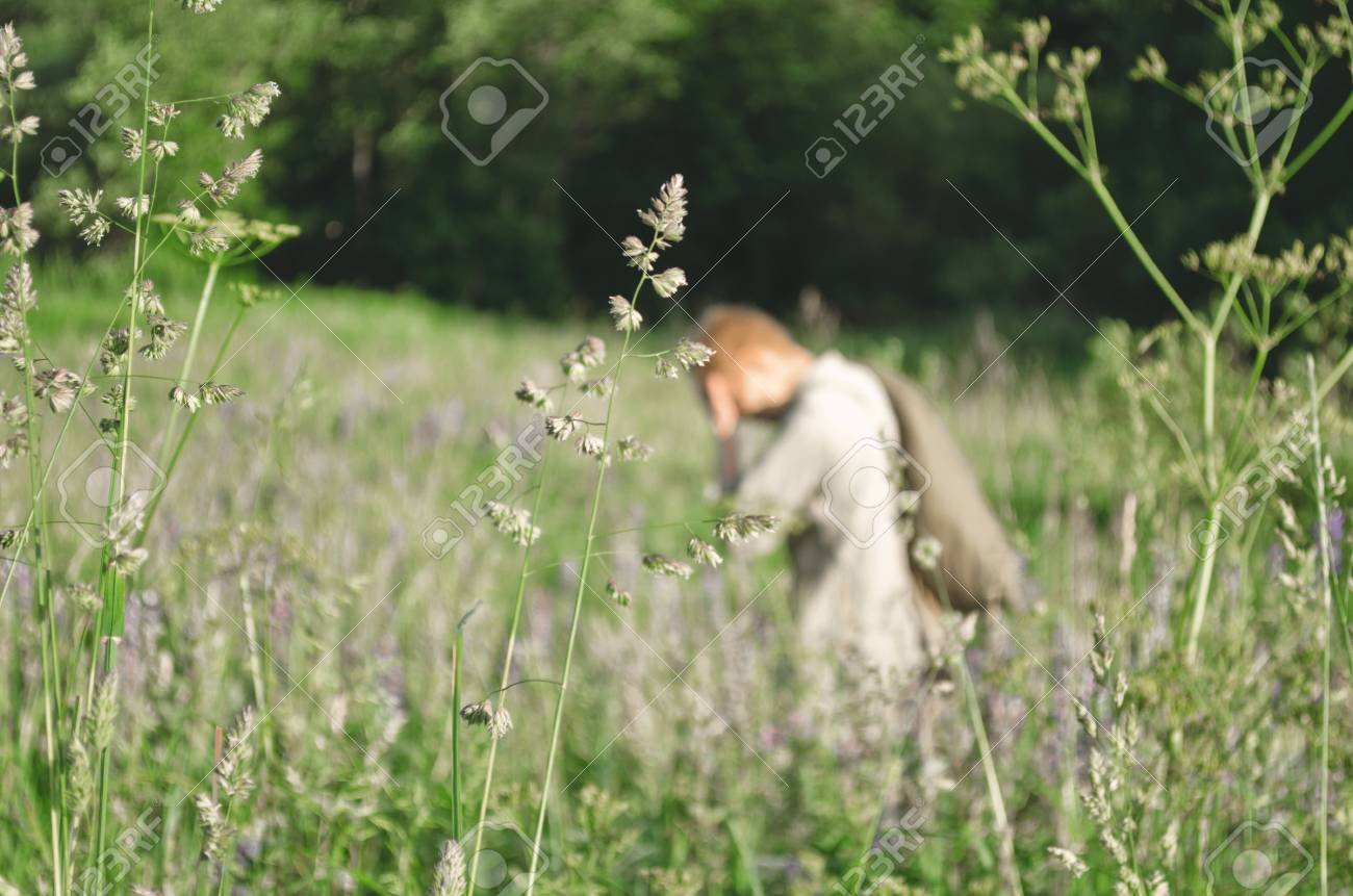 Soldier Walks Among The Tall Grasses And Carries A Large Bag