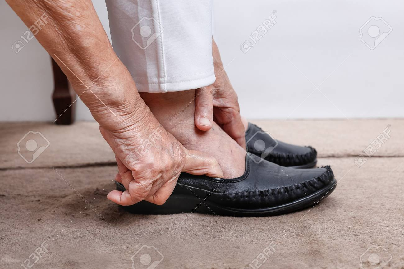 Elderly Woman Putting On Shoes Stock