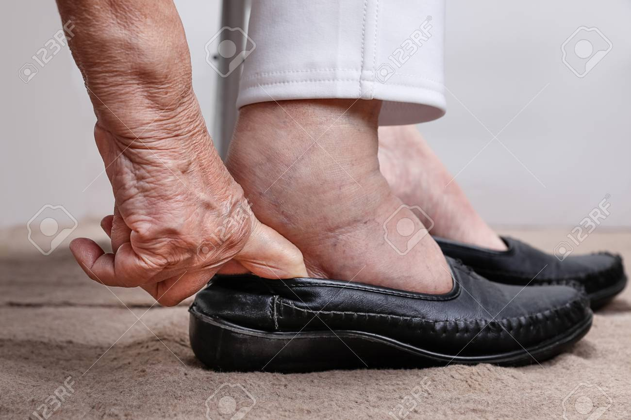 da30c48cadb9 Elderly woman swollen feet putting on shoes