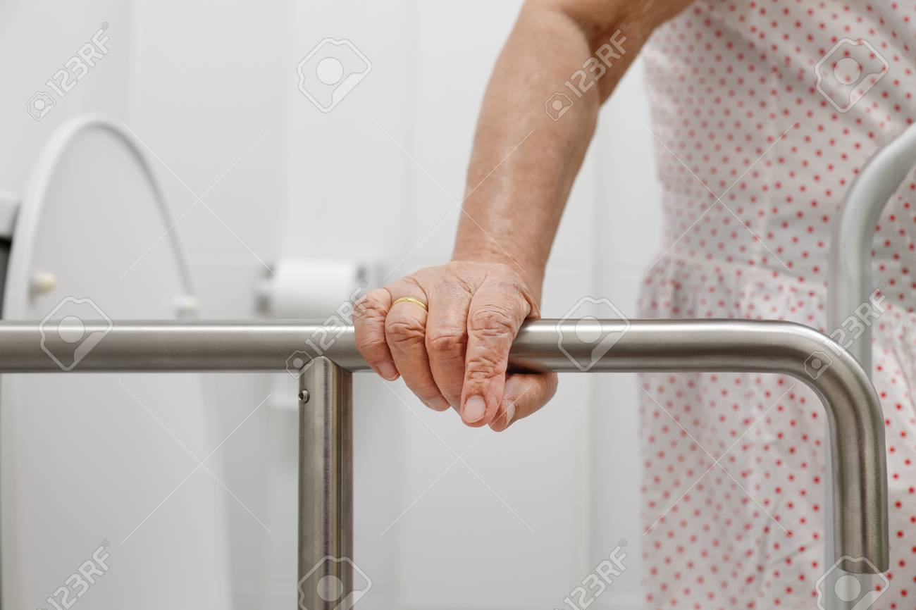Elderly Woman Holding On Handrail In Toilet. Stock Photo, Picture ...