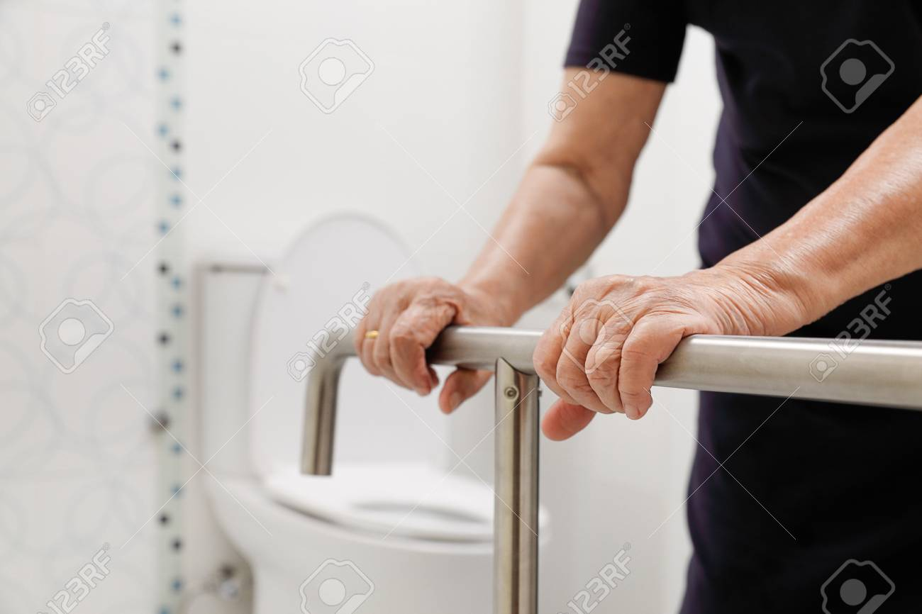 Elderly Woman Holding On Handrail In Bathroom. Stock Photo, Picture ...