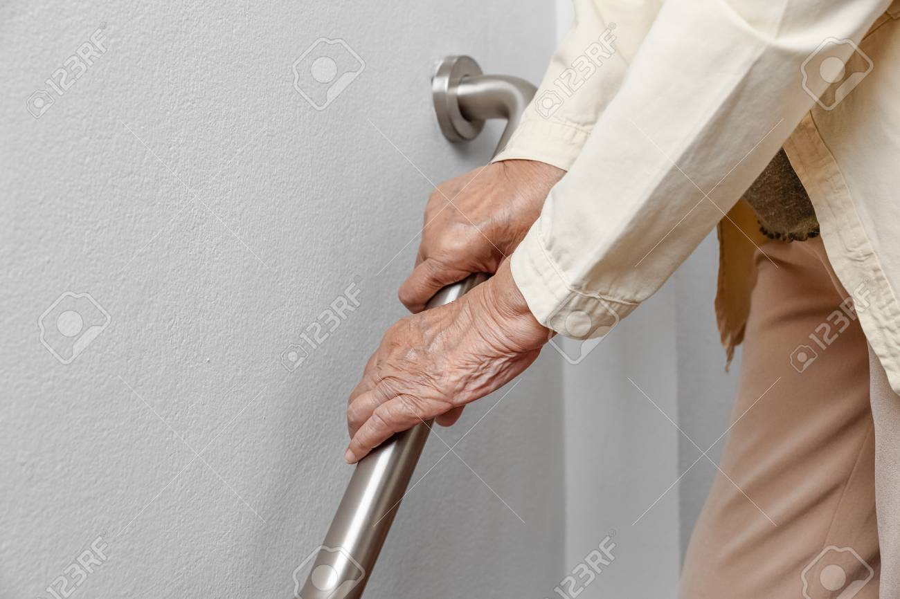 Elderly woman holding on handrail for safety walk steps - 103855986